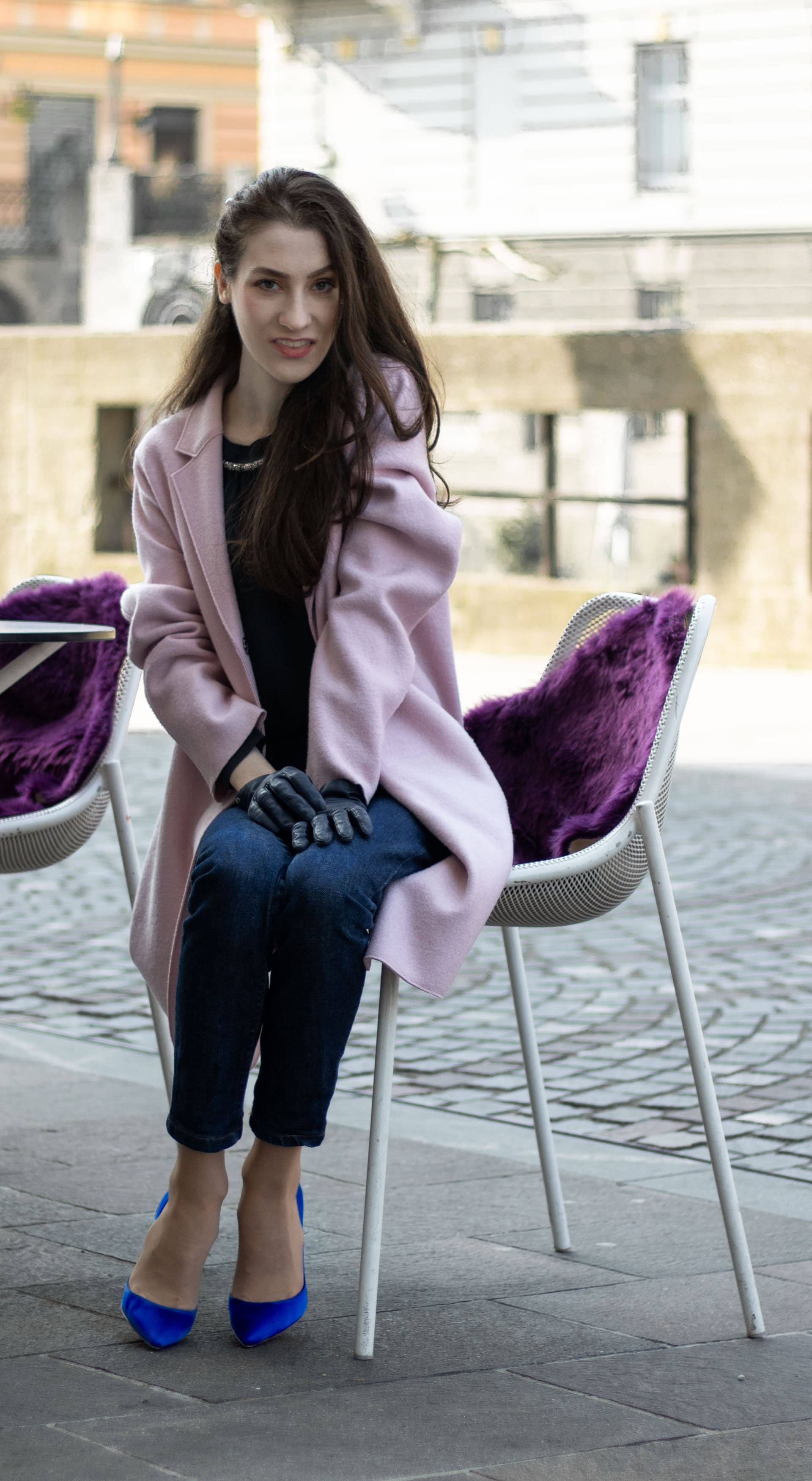 Must follow Fashion Blogger Veronika Lipar of Brunette from Wall Street dressed in oversize pink Harris Wharf London coat A.P.C. Paris dark blue denim jeans Gianvito Rossi blue court shoes black top handle bag Forzieri blue leather gloves pearl hairpin sitting on the street