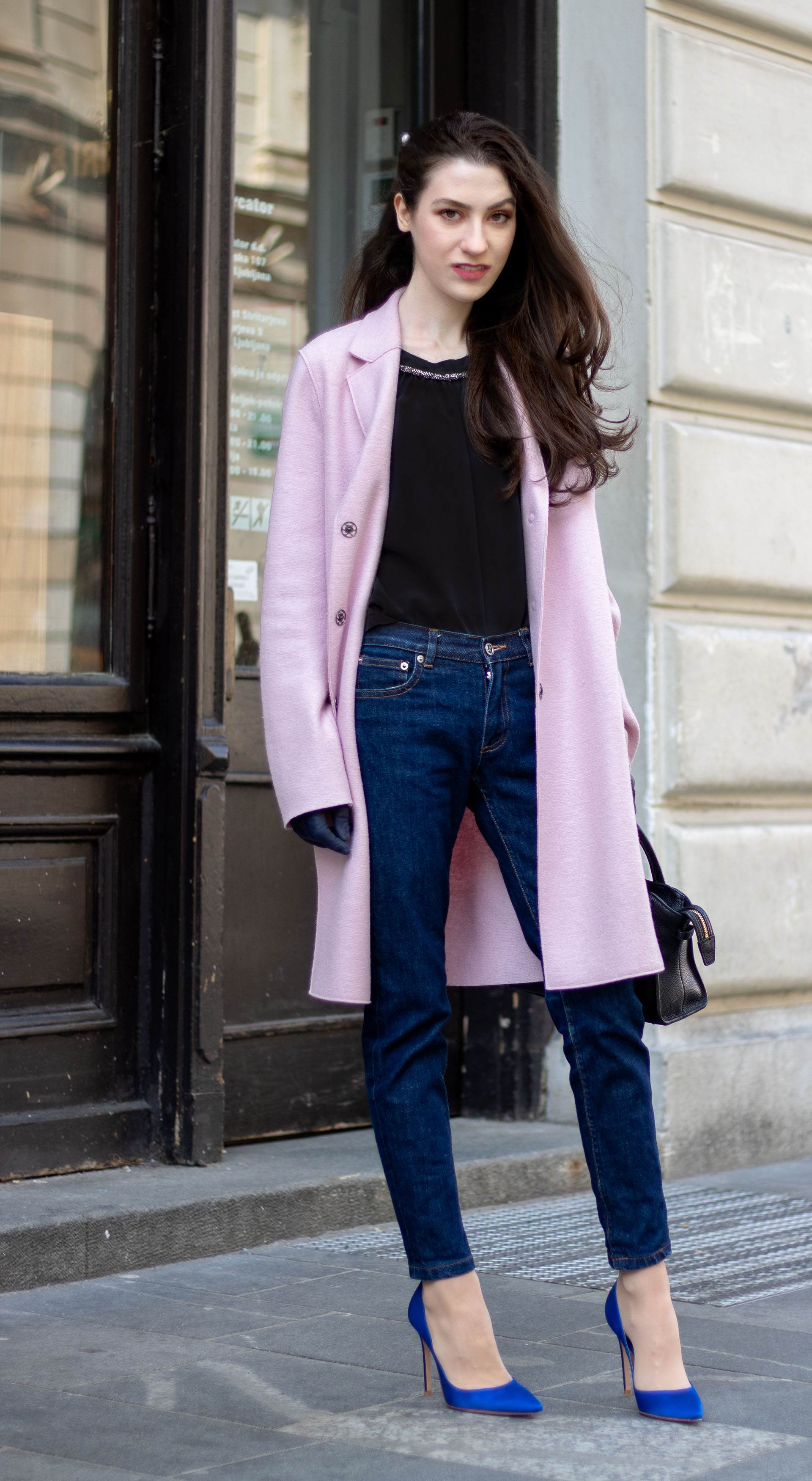 Must follow Fashion Blogger Veronika Lipar of Brunette from Wall Street dressed in oversize pink Harris Wharf London coat A.P.C. Paris dark blue denim jeans Gianvito Rossi blue pumps black top handle bag Forzieri blue leather gloves pearl hairpin standing on the street