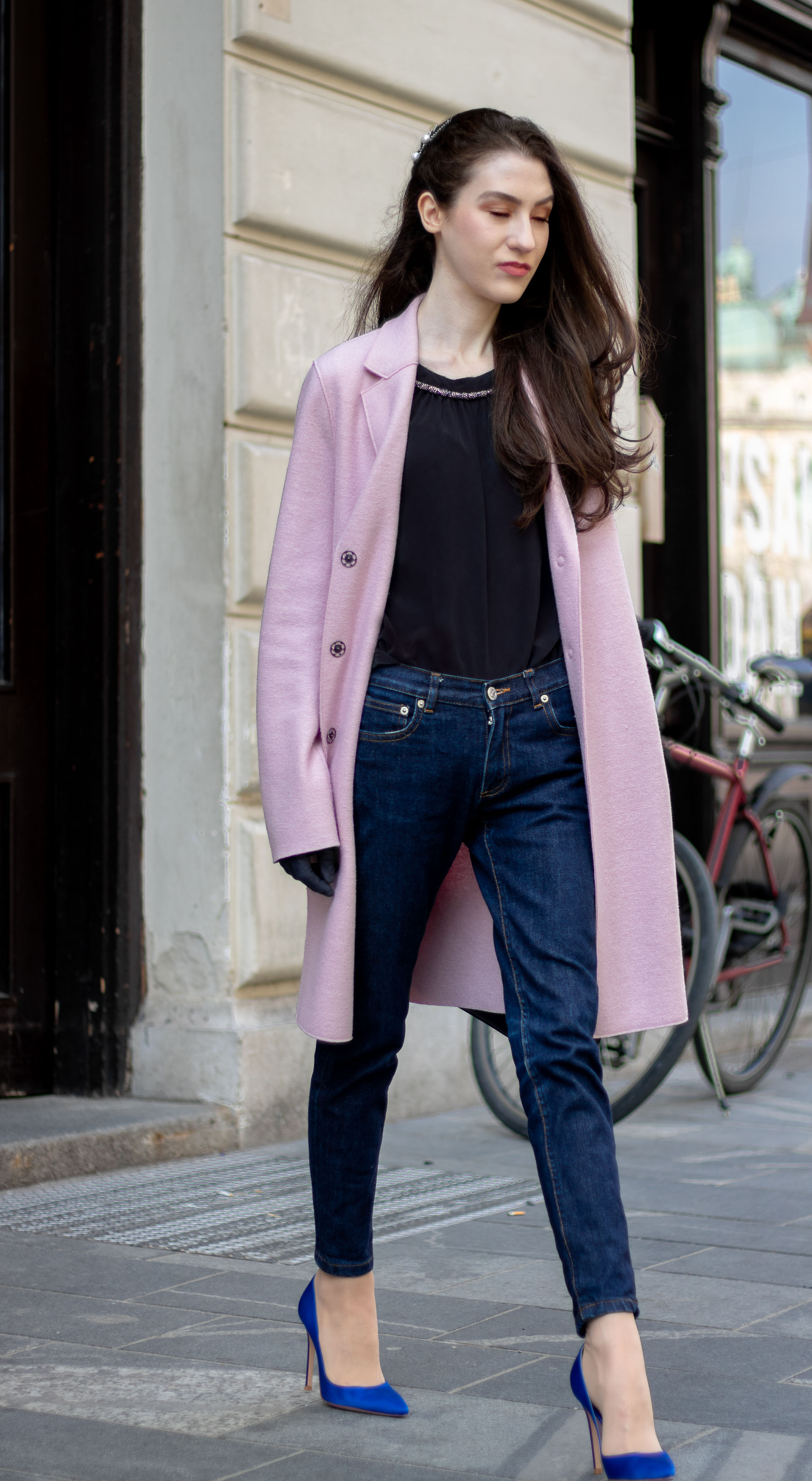 Must follow Fashion Blogger Veronika Lipar of Brunette from Wall Street dressed in loose pink Harris Wharf London coat A.P.C. Paris dark blue denim jeans Gianvito Rossi blue heels black top handle bag Forzieri blue leather gloves pearl hairpin walking down the street