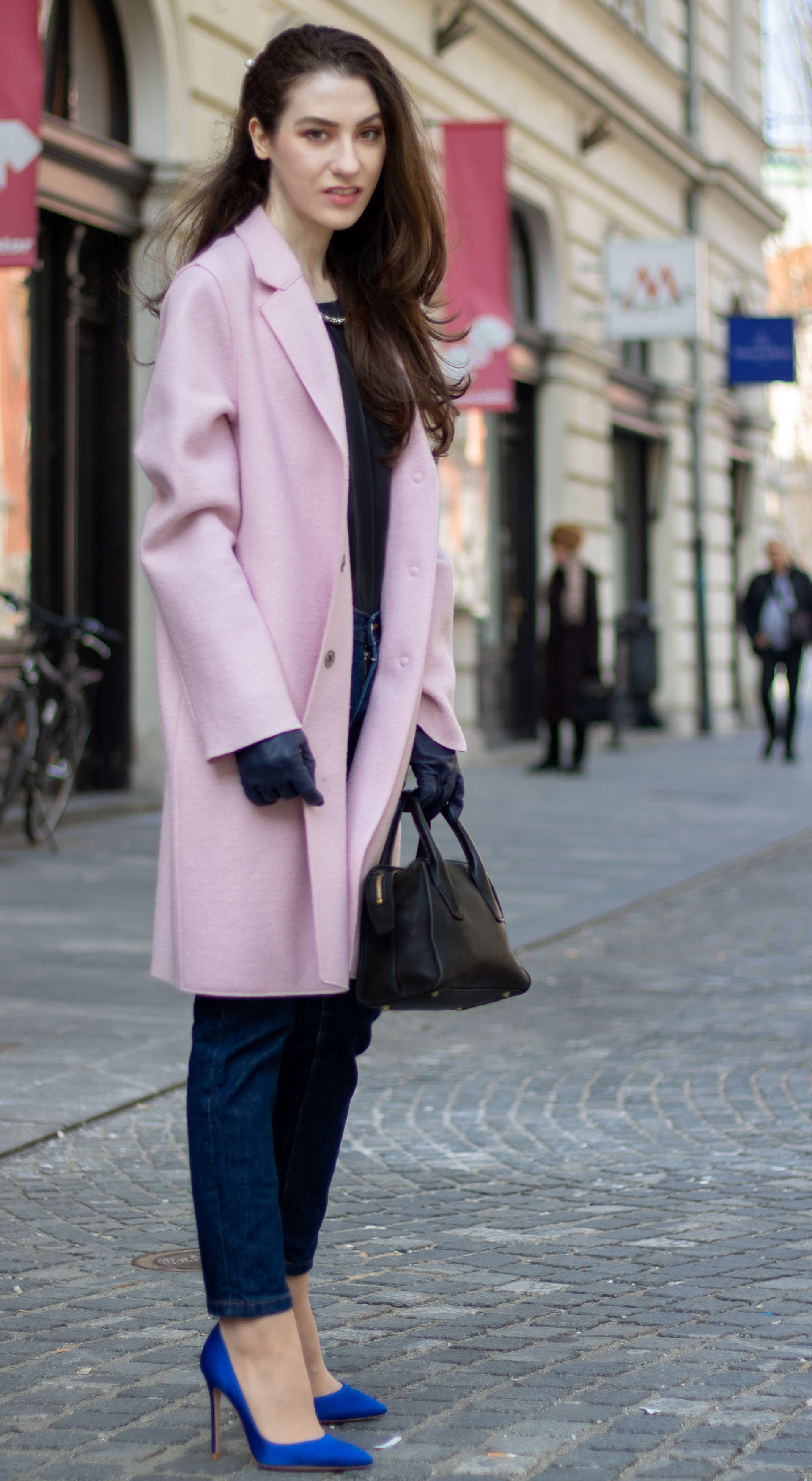 Must follow Fashion Blogger Veronika Lipar of Brunette from Wall Street wearing loose pink Harris Wharf London coat A.P.C. Paris dark blue denim jeans Gianvito Rossi blue heels black top handle bag Forzieri blue leather gloves pearl hairpin standing on the street