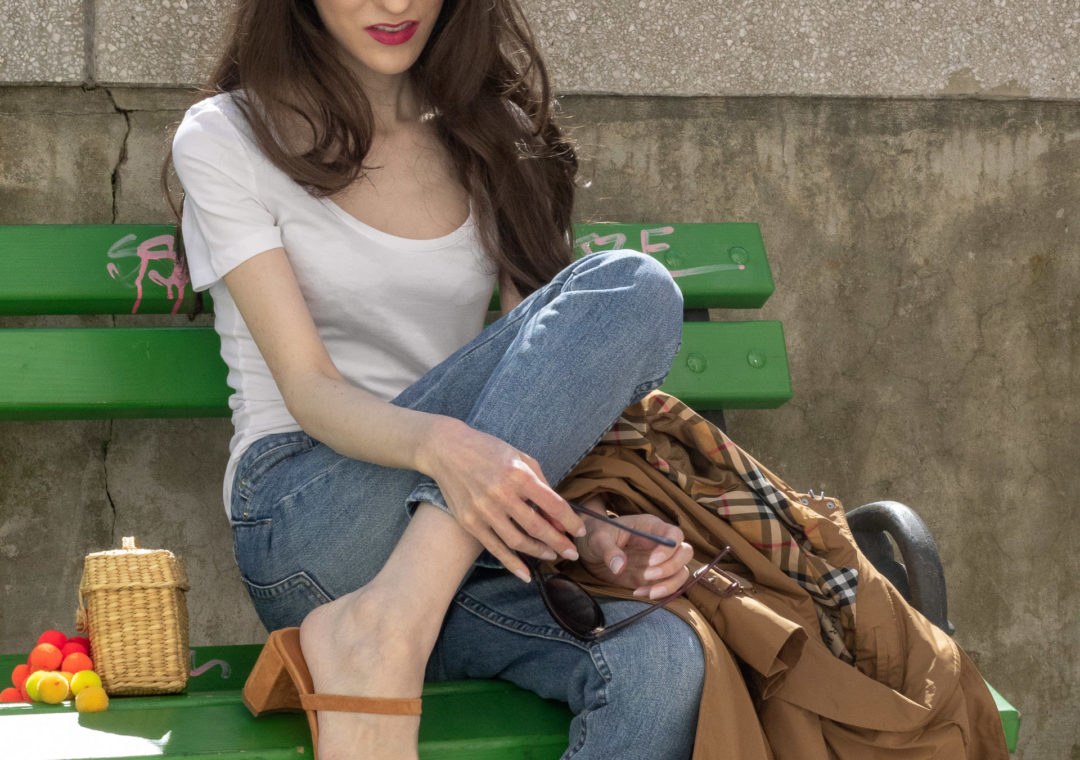 Must follow Slovenian Fashion Blogger Veronika Lipar of Brunette from Wall Street wearing by Far Tanya Nude sandals A.P.C. light blue jeans and a white T-shirt under camel Burberry Kensington Trench coat Nannacay raffia basket bag long hair sitting on a green bench
