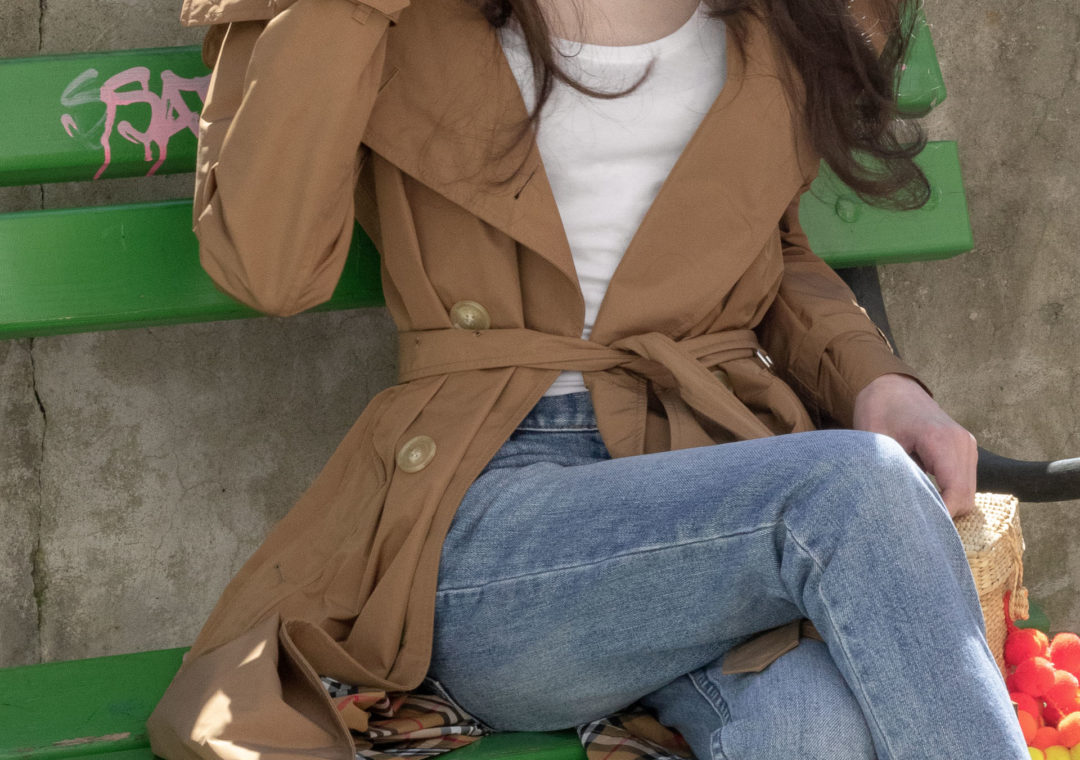 Must follow Slovenian Fashion Blogger Veronika Lipar of Brunette from Wall Street dressed in A.P.C. light blue jeans and a white T-shirt under camel Burberry Kensington Trench coat Nannacay raffia basket bag sitting on a green bench