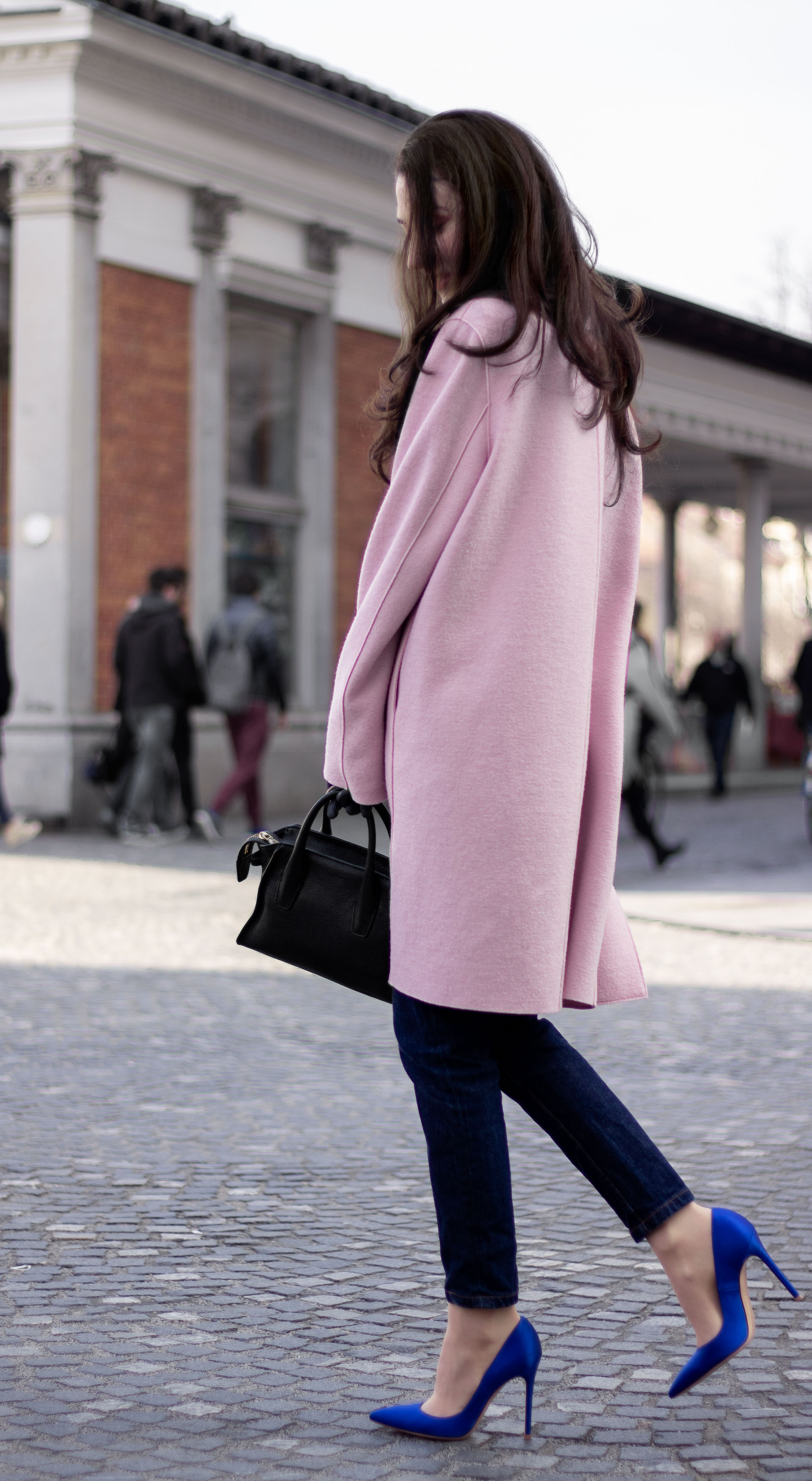 Must follow Fashion Blogger Veronika Lipar of Brunette from Wall Street dressed in oversize pink Harris Wharf London coat A.P.C. Paris dark blue denim jeans Gianvito Rossi blue court shoes black top handle bag Forzieri blue leather gloves pearl hairpin on the street