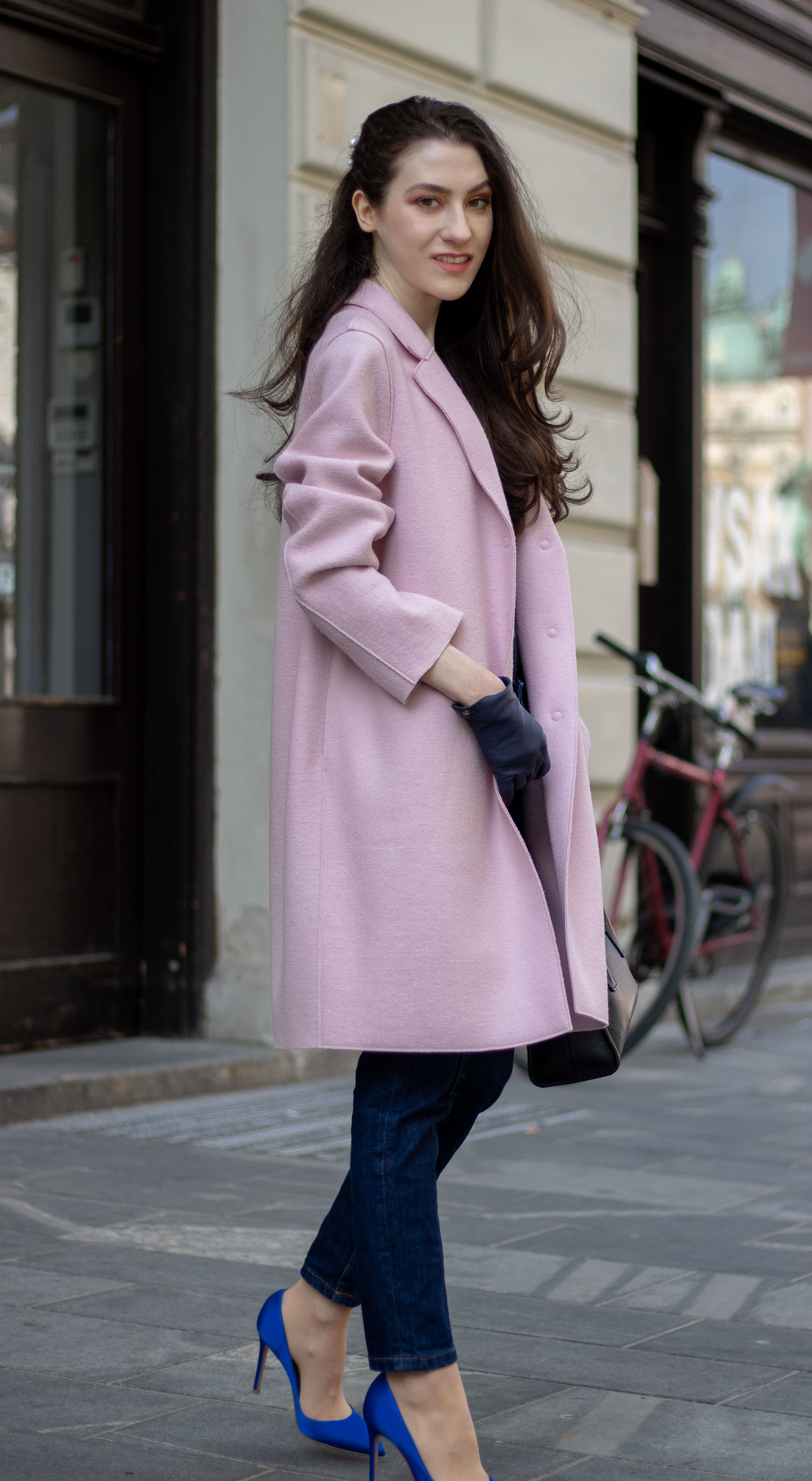 Must follow Fashion Blogger Veronika Lipar of Brunette from Wall Street dressed in oversize pink Harris Wharf London coat A.P.C. Paris dark blue denim jeans Gianvito Rossi blue court shoes black top handle bag Forzieri blue leather gloves pearl hairpin standing on the street
