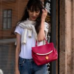 Brunette from Wall Street Veronika Lipar wearing white sweater set white T-shirt blue jeans pink top handle bag in fall