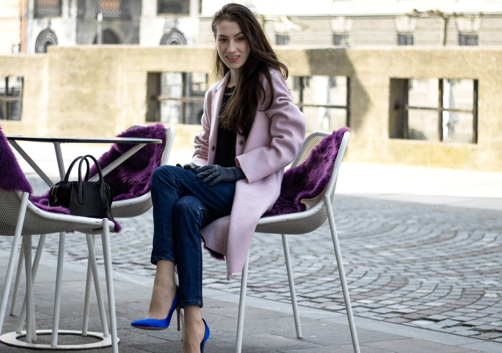 Must follow Fashion Blogger Veronika Lipar of Brunette from Wall Street dressed in loose pink Harris Wharf London coat A.P.C. Paris dark blue denim jeans Gianvito Rossi blue pumps black top handle bag Forzieri blue leather gloves pearl hairpin sitting at the table on the street