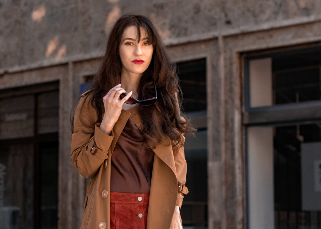 Influential Fashion Blogger Veronika Lipar of Brunette from Wall street wearing camel Burberry trench coat tortoise sunglasses Theory button front camel suede skirt brown cowl neck silk top in the city