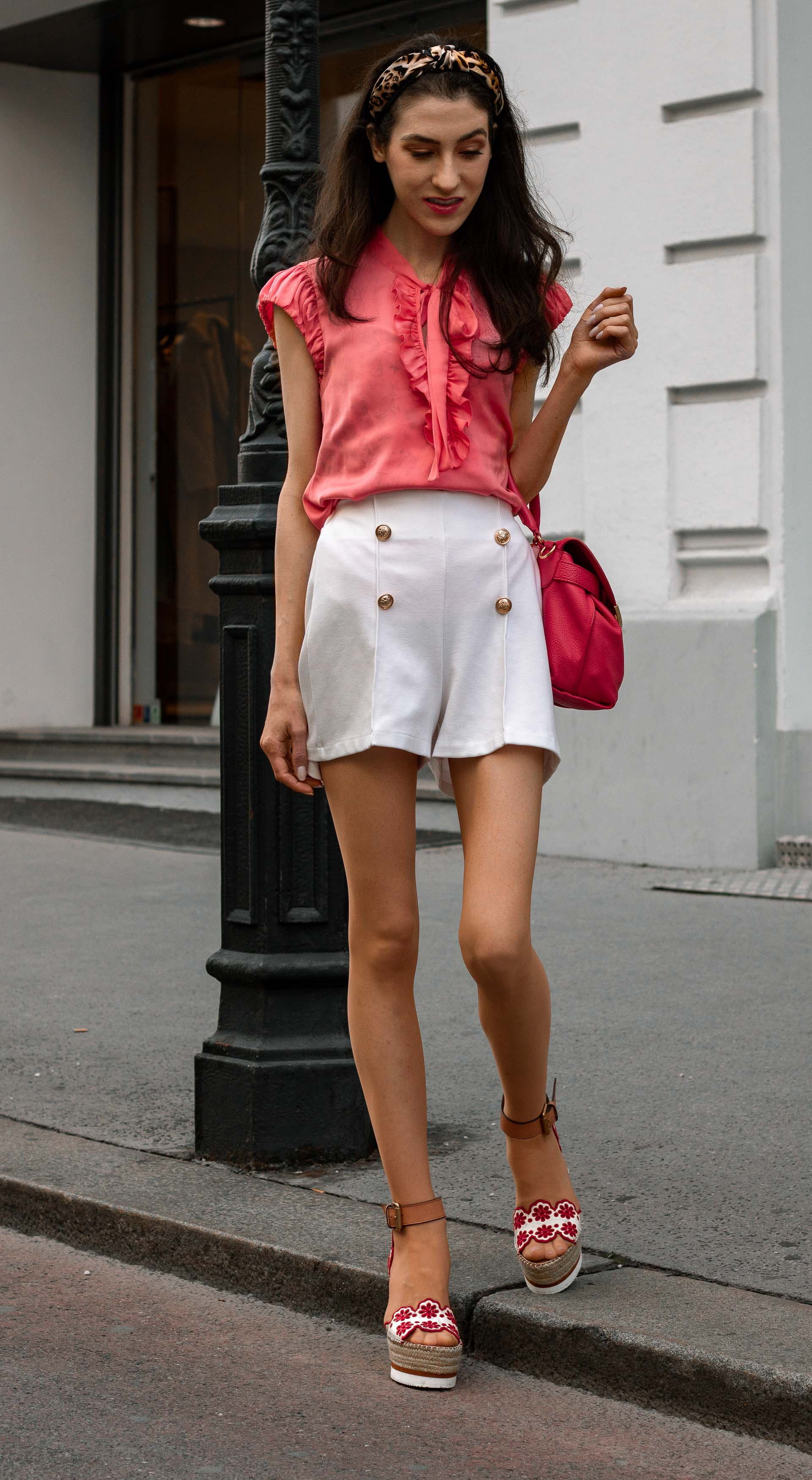 Gossip Girl Veronika Lipar Fashion Blogger of Brunette from Wall Street wearing peachy orange pussy-bow tie blouse white shorts leopard print headband pink top handle bag See by Chloe wedge espadrille sandals