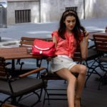 Gossip Girl Veronika Lipar Fashion Blogger of Brunette from Wall Street dressed in peachy orange pussy-bow tie blouse white shorts leopard print headband pink top sitting at the table outside at brunch