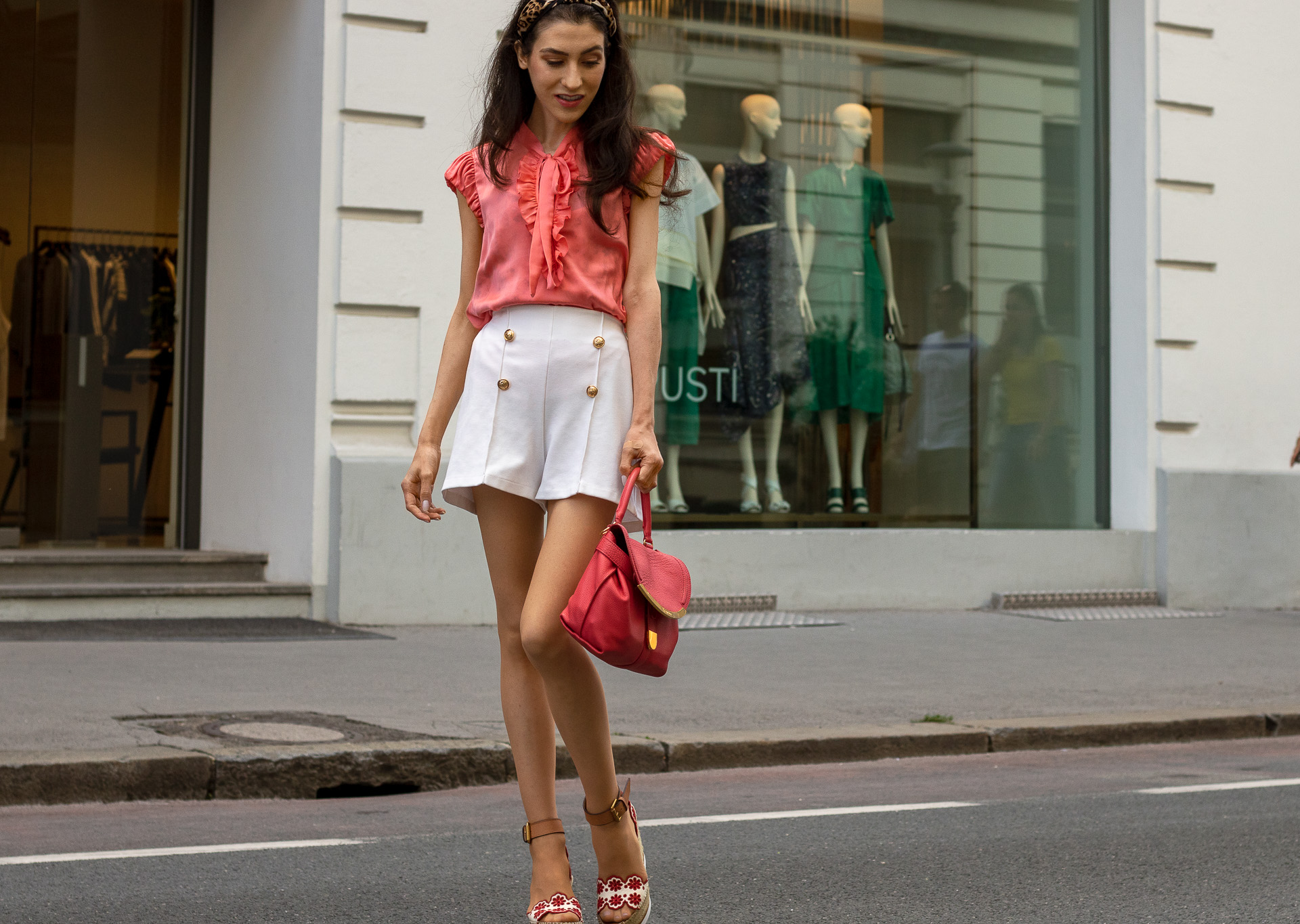 Gossip Girl Veronika Lipar Fashion Blogger of Brunette from Wall Street dressed in peachy orange pussy-bow tie blouse white shorts leopard print headband pink top handle bag See by Chloe wedge espadrille sandals walking down the street