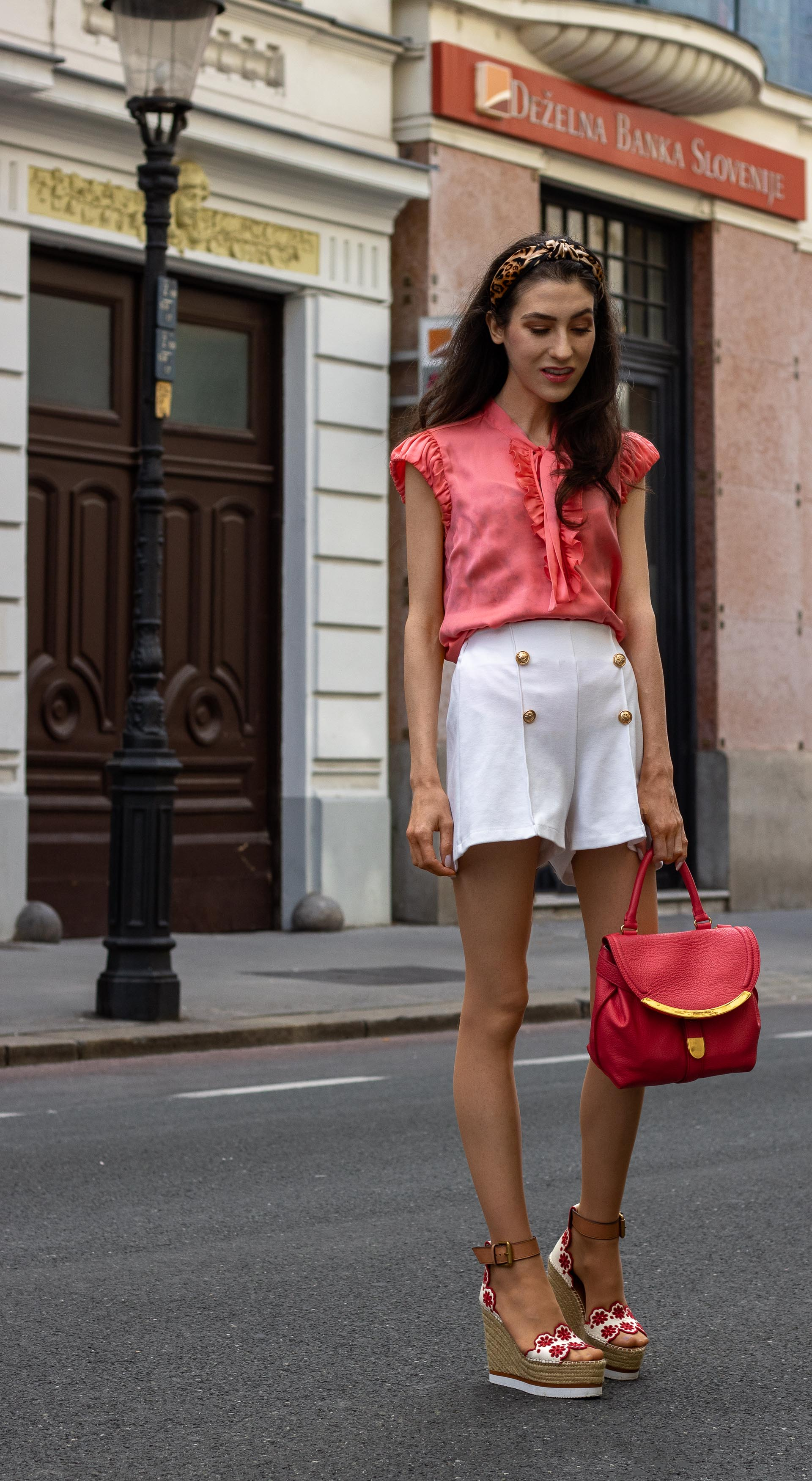 Gossip Girl Veronika Lipar Fashion Blogger of Brunette from Wall Street wearing peachy orange pussy-bow tie blouse white shorts leopard print headband pink top handle bag See by Chloe wedge espadrilles