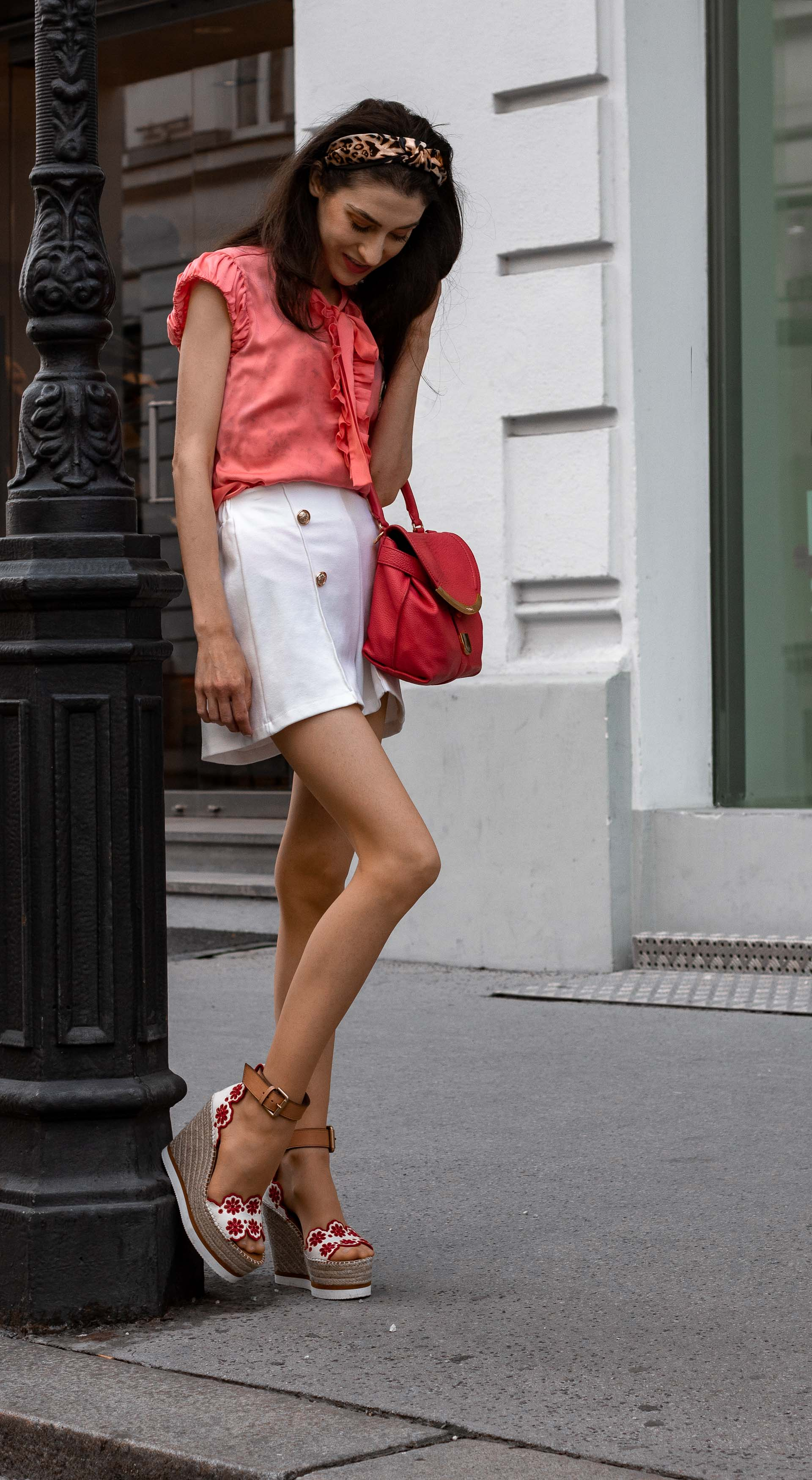 Gossip Girl Veronika Lipar Fashion Blogger of Brunette from Wall Street wearing peachy orange pussy-bow tie blouse white shorts leopard print headband pink top handle bag See by Chloe wedge espadrille sandals leaning on the street lamp