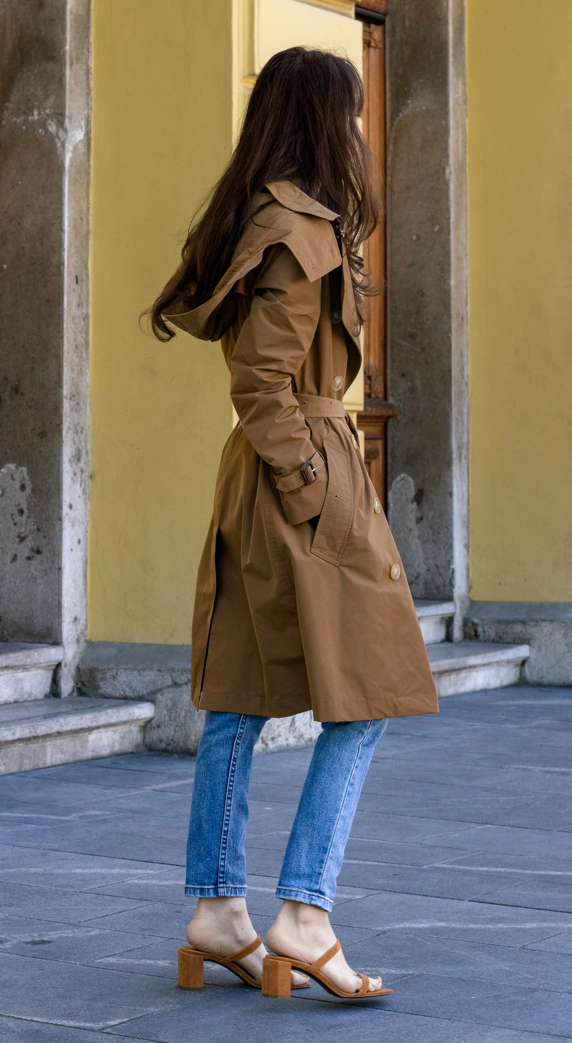 Must follow Fashion Blogger Veronika Lipar of Brunette from Wall Street dressed in Burberry trench coat over clothes we wear around the house A.P.C. Paris blue denim jeans white T-shirt By Far sandals Nannacay basket bag sunglasses on a rainy summer day