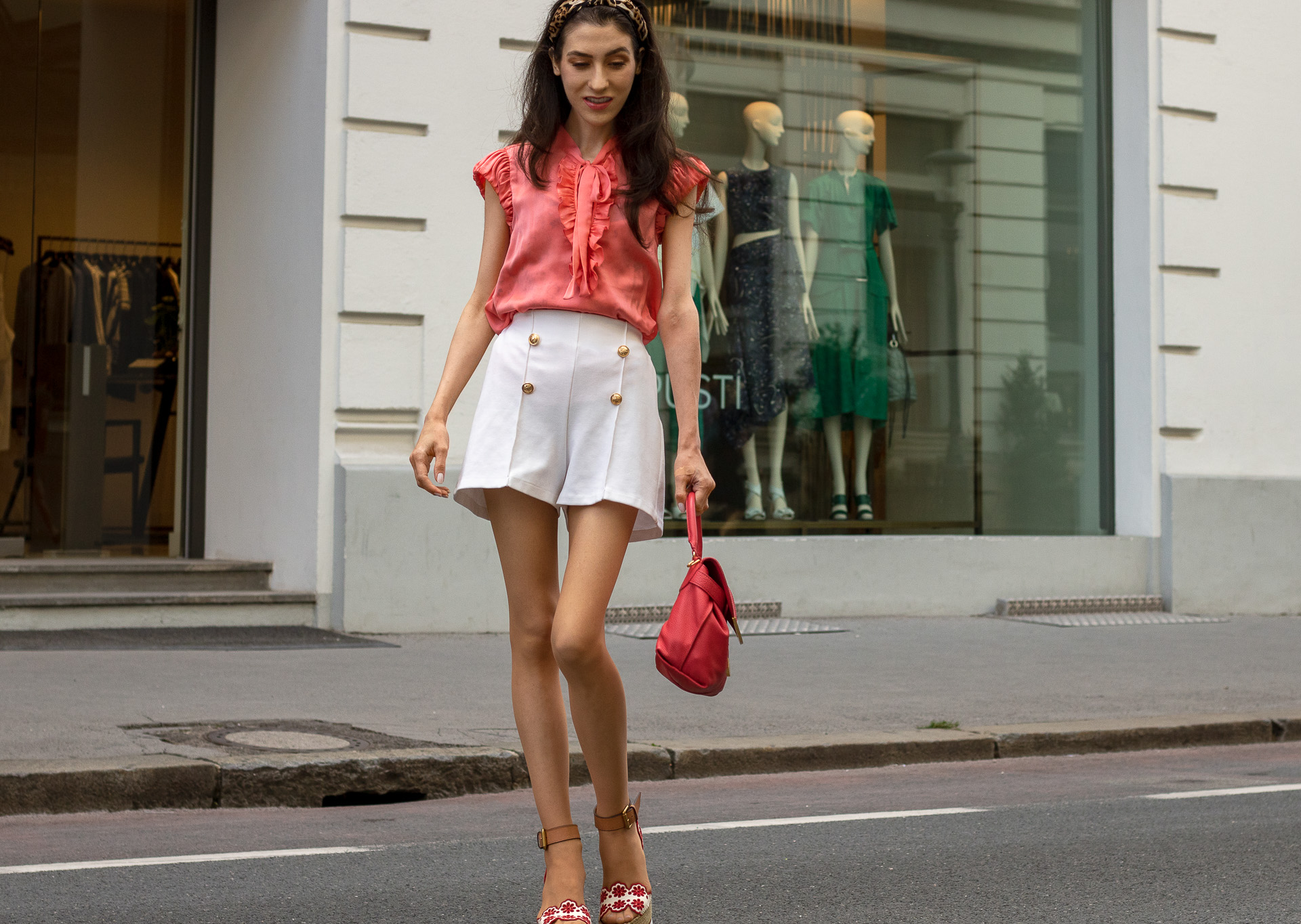 Gossip Girl Veronika Lipar Fashion Blogger of Brunette from Wall Street wearing peachy orange pussy-bow tie blouse white shorts leopard print headband pink top handle bag See by Chloe wedge espadrille sandals walking down the street