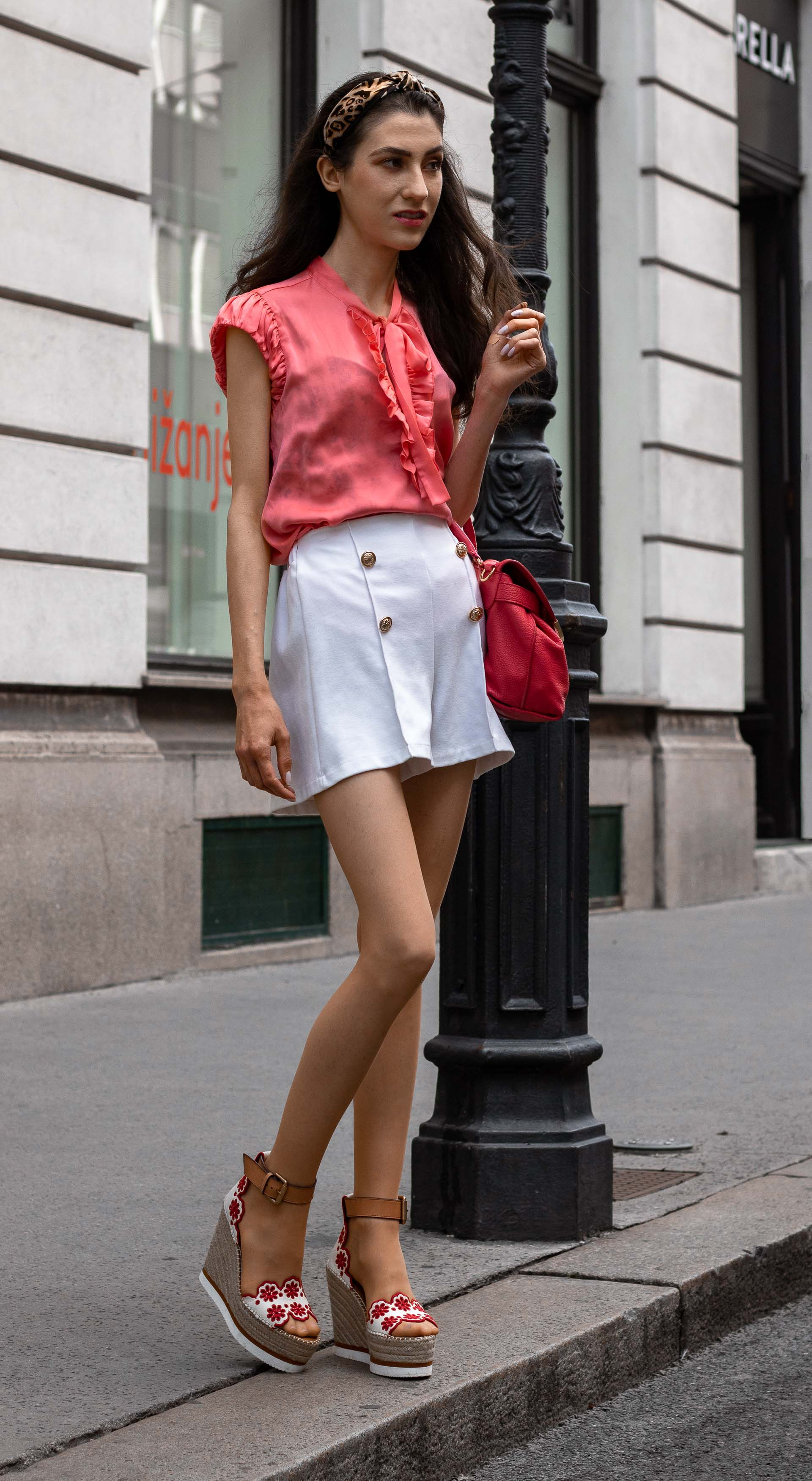 Gossip Girl Veronika Lipar Fashion Blogger of Brunette from Wall Street wearing peachy orange pussy-bow tie blouse white shorts leopard print headband pink top handle bag See by Chloe wedge espadrille sandals standing by the street lamp