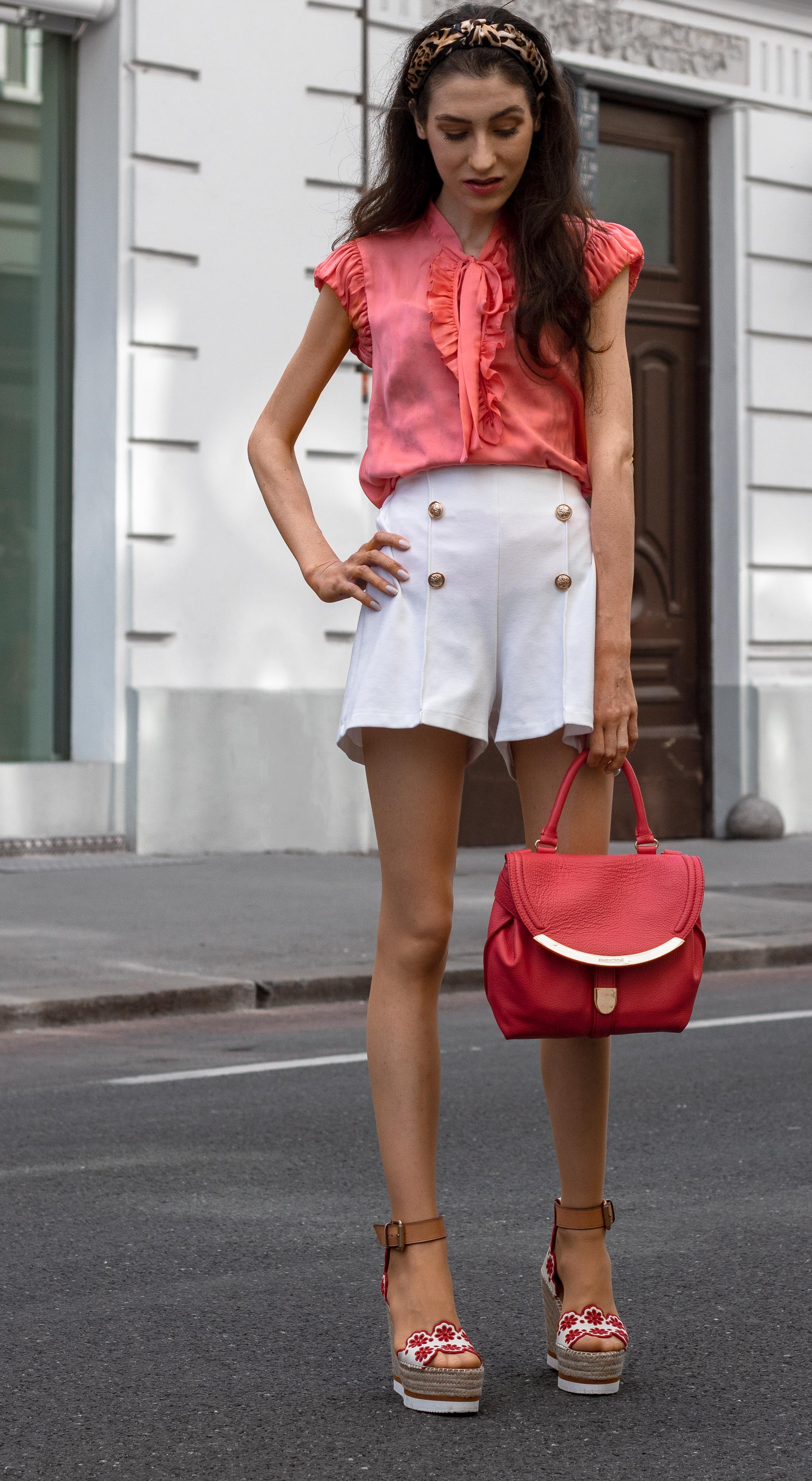 Gossip Girl Veronika Lipar Fashion Blogger of Brunette from Wall Street dressed in peachy orange pussy-bow tie blouse white shorts leopard print headband pink top handle bag See by Chloe wedge espadrilles