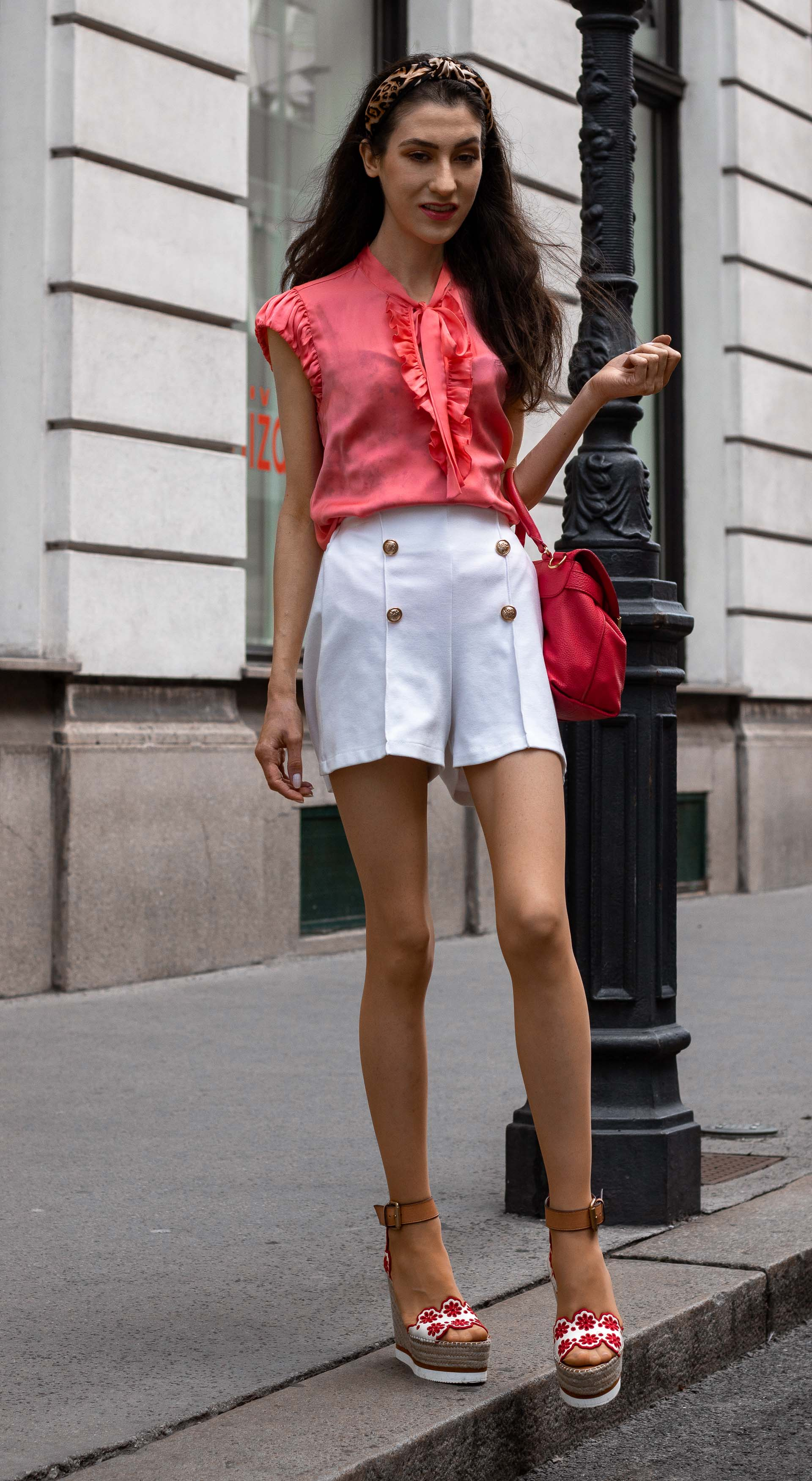 Gossip Girl Veronika Lipar Fashion Blogger of Brunette from Wall Street dressed in peachy orange pussy-bow tie blouse white shorts leopard print headband pink top handle bag See by Chloe wedges