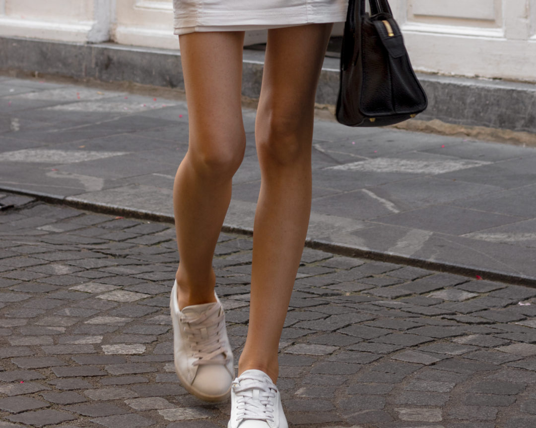 Beautiful Fashion Blogger Veronika Lipar of Brunette from Wall Street wearing in short white dress white sneakers walking down the street