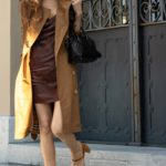 Must follow Fashion Blogger Veronika Lipar of Brunette from Wall Street dressed in Burberry trench coat brown slip dress By Far suede sandals leaving home