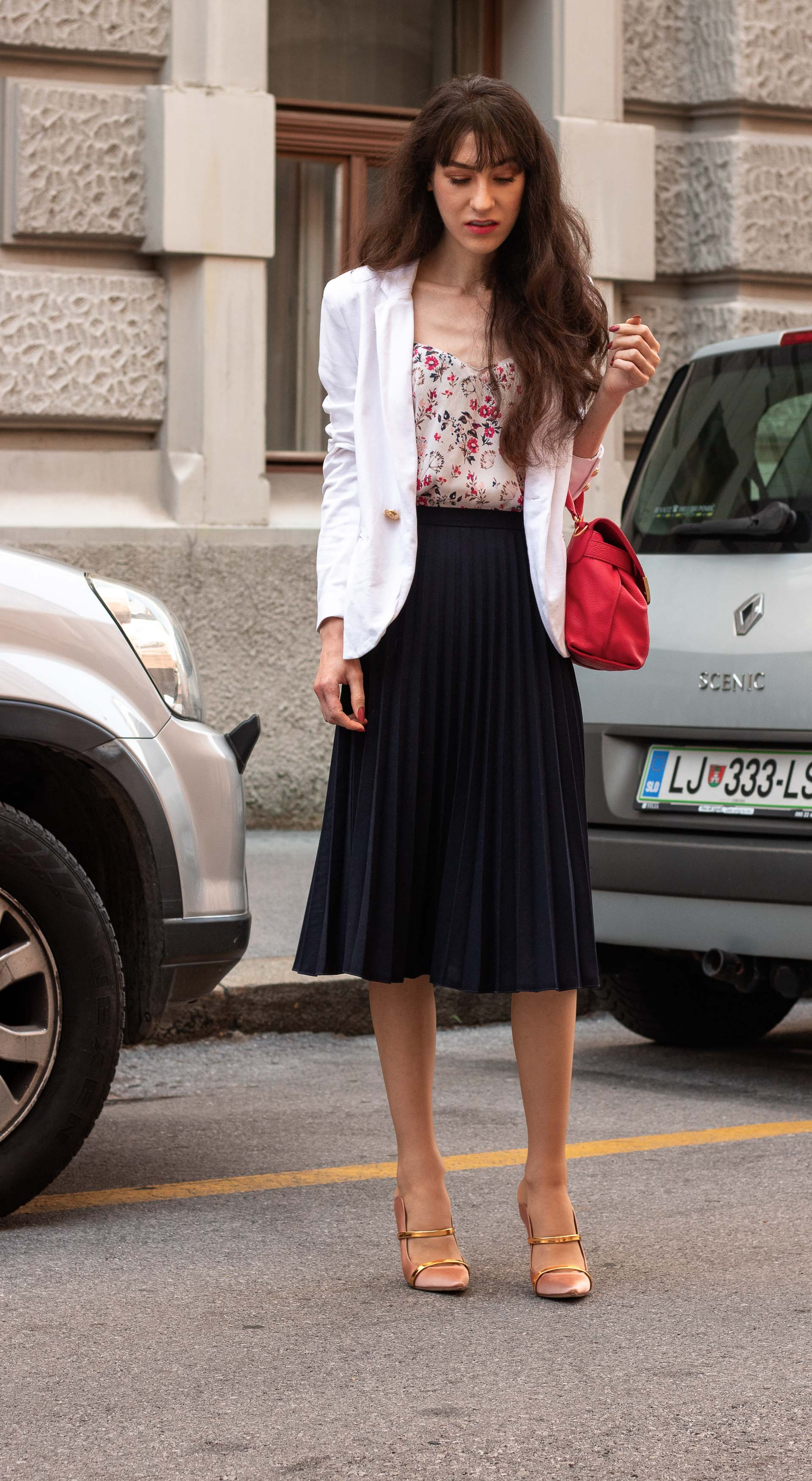 IT Girl Fashion Blogger Veronika Lipar of Brunette from Wall Street wearing white blazer pleated midi skirt camisole pink top handle bag Malone Souliers mules going to work in summer