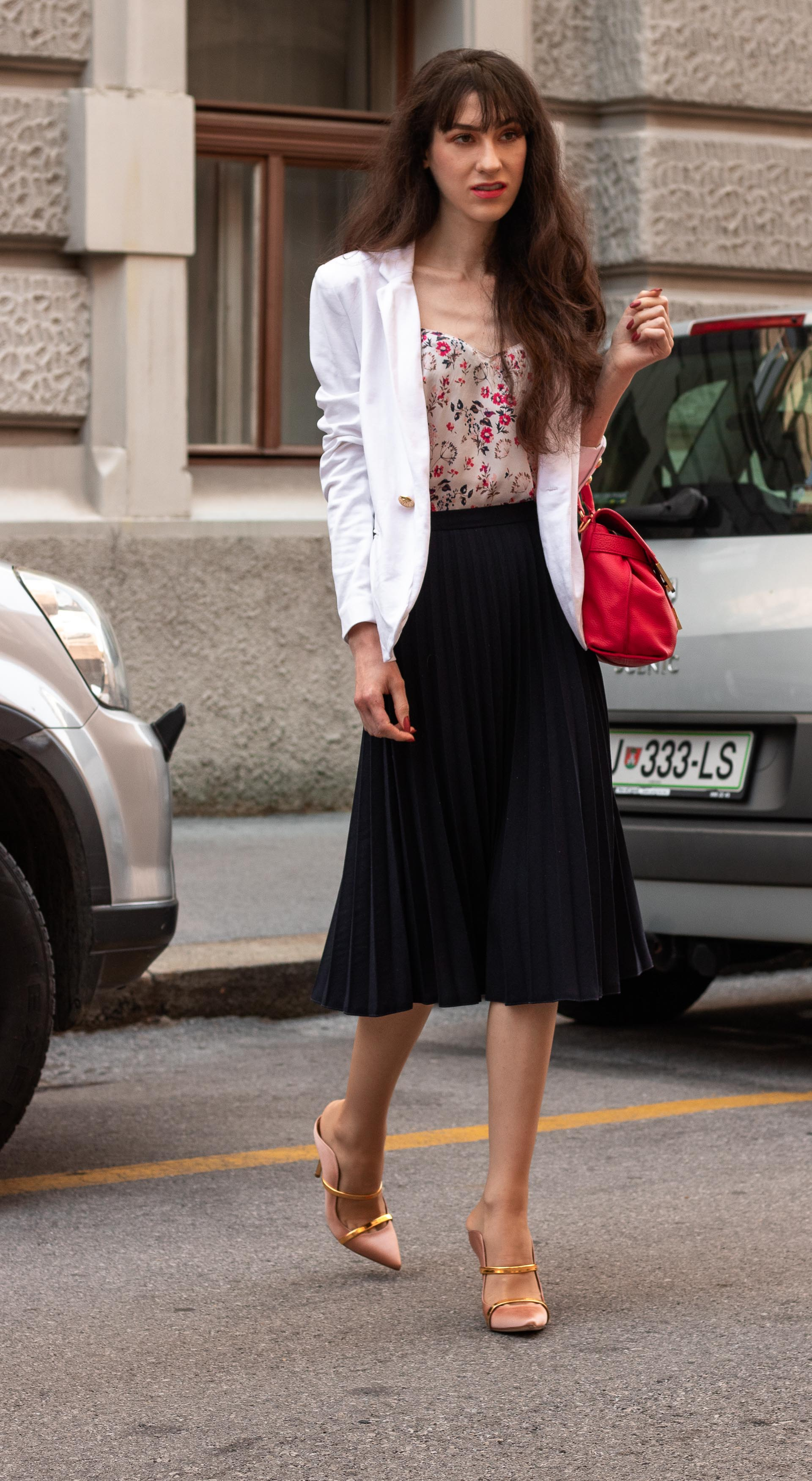 IT Girl Fashion Blogger Veronika Lipar of Brunette from Wall Street wearing white blazer pleated midi skirt camisole pink top handle bag Malone Souliers mules for work in summer
