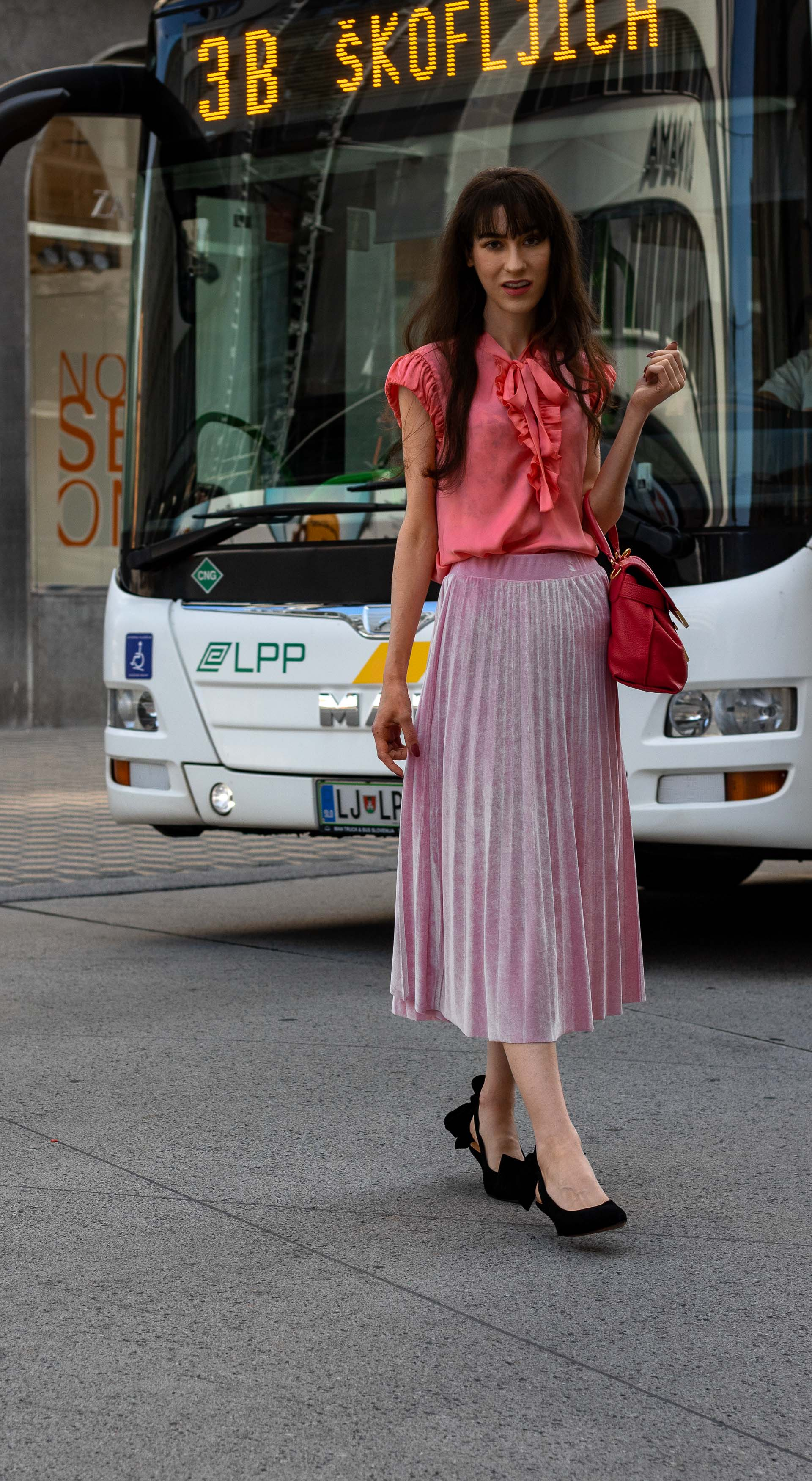 IT Girl Fashion Blogger Veronika Lipar of Brunette from Wall Street wearing coral pink floppy tie blouse pink pleated midi skirt Ganni slingbacks pink top handle bag going to work in summer