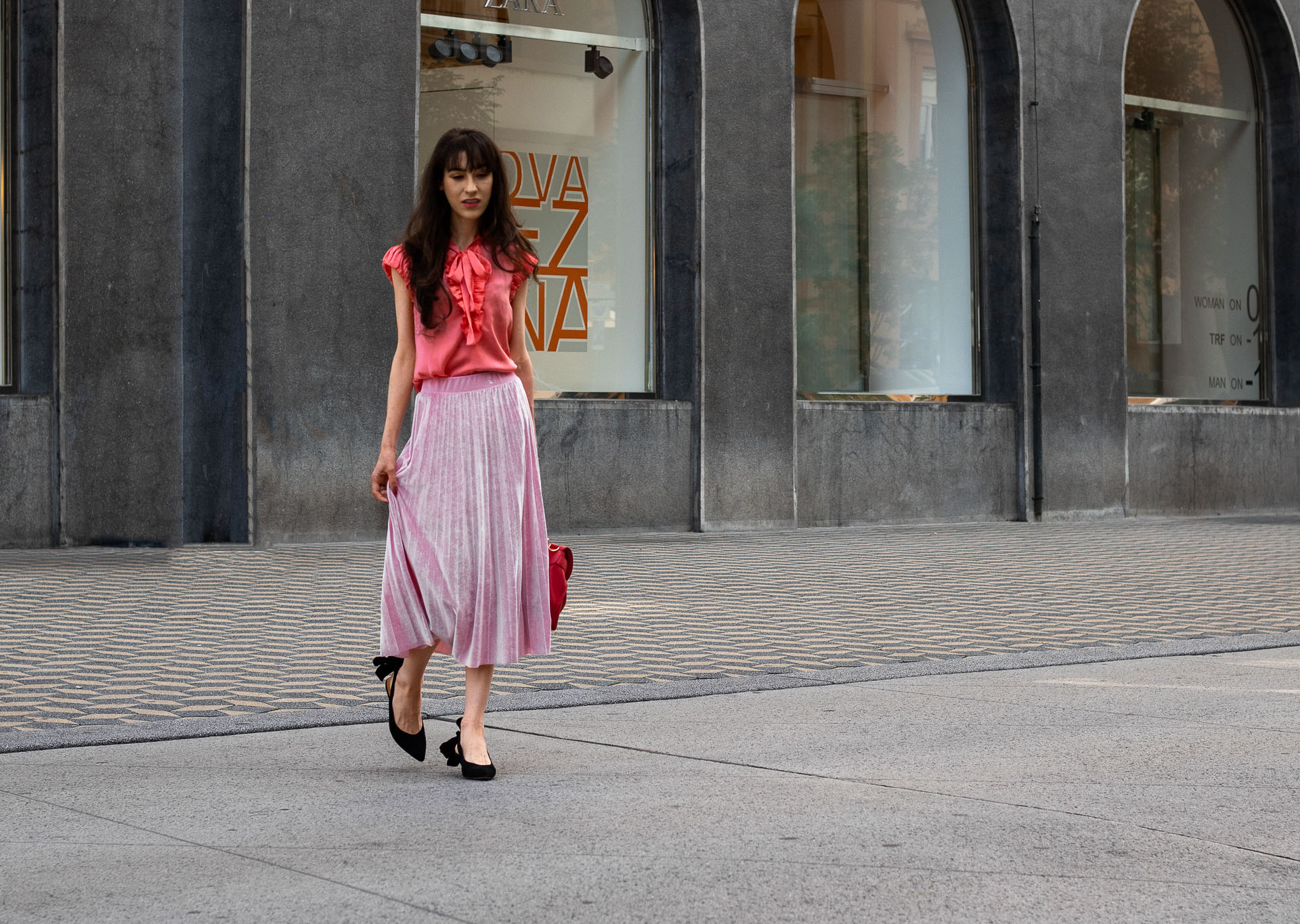 IT Girl Fashion Blogger Veronika Lipar of Brunette from Wall Street wearing coral pink floppy tie blouse pink pleated midi skirt Ganni slingbacks pink top handle bag for work in summer