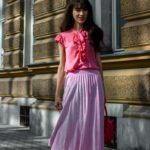Fashion Blogger Veronika Lipar of Brunette from Wall Street wearing pink pleated midi skirt, coral pink floppy tie blouse Stuart Weitzman sandals pink top handle bag for Sunday mass at the church in summer