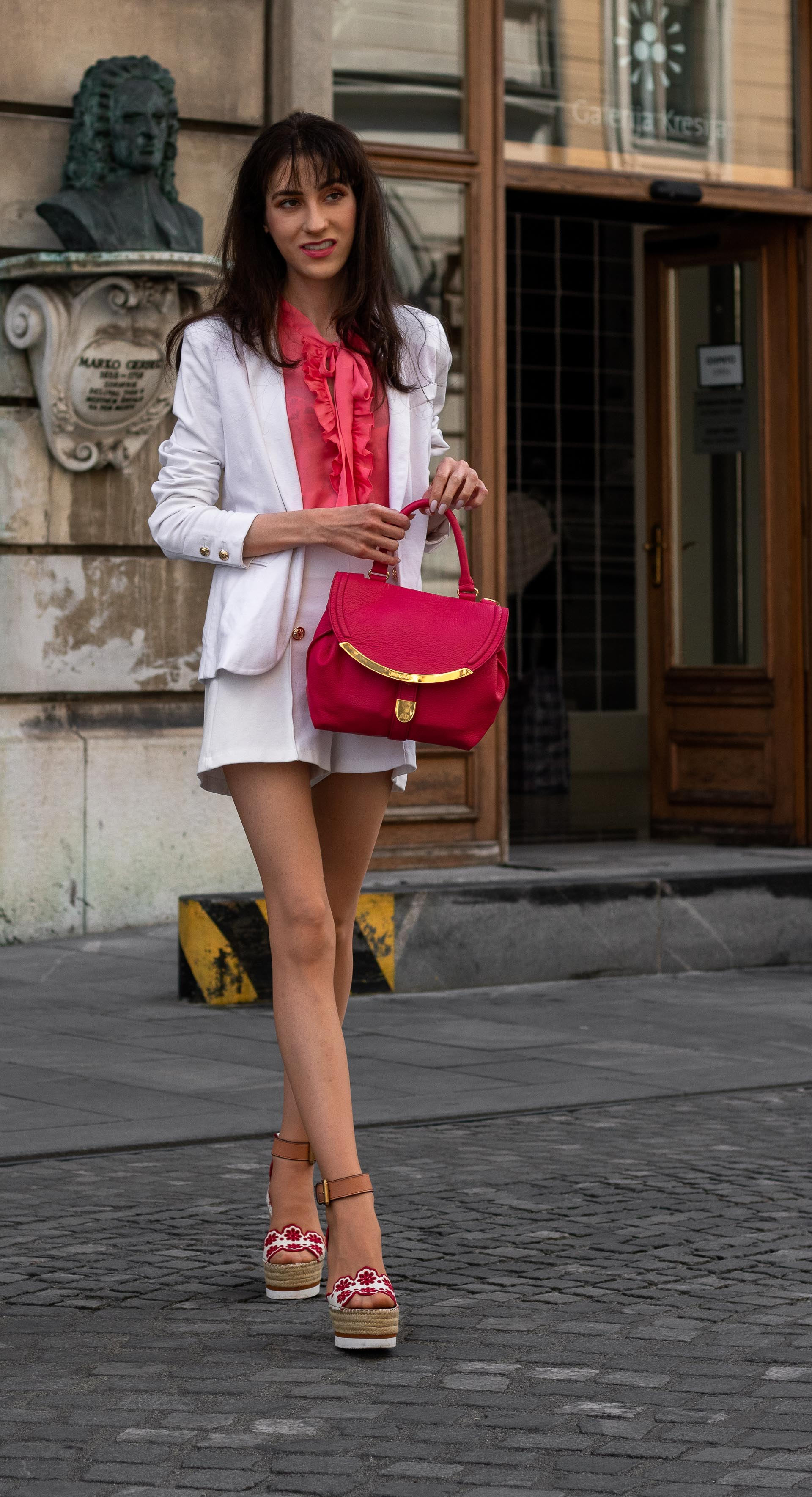 Fashion Blogger Veronika Lipar of Brunette from Wall Street dressed in See by Chloé wedge espadrilles white shorts white blazer orange floppy tie blouse pink top handle bag in the city
