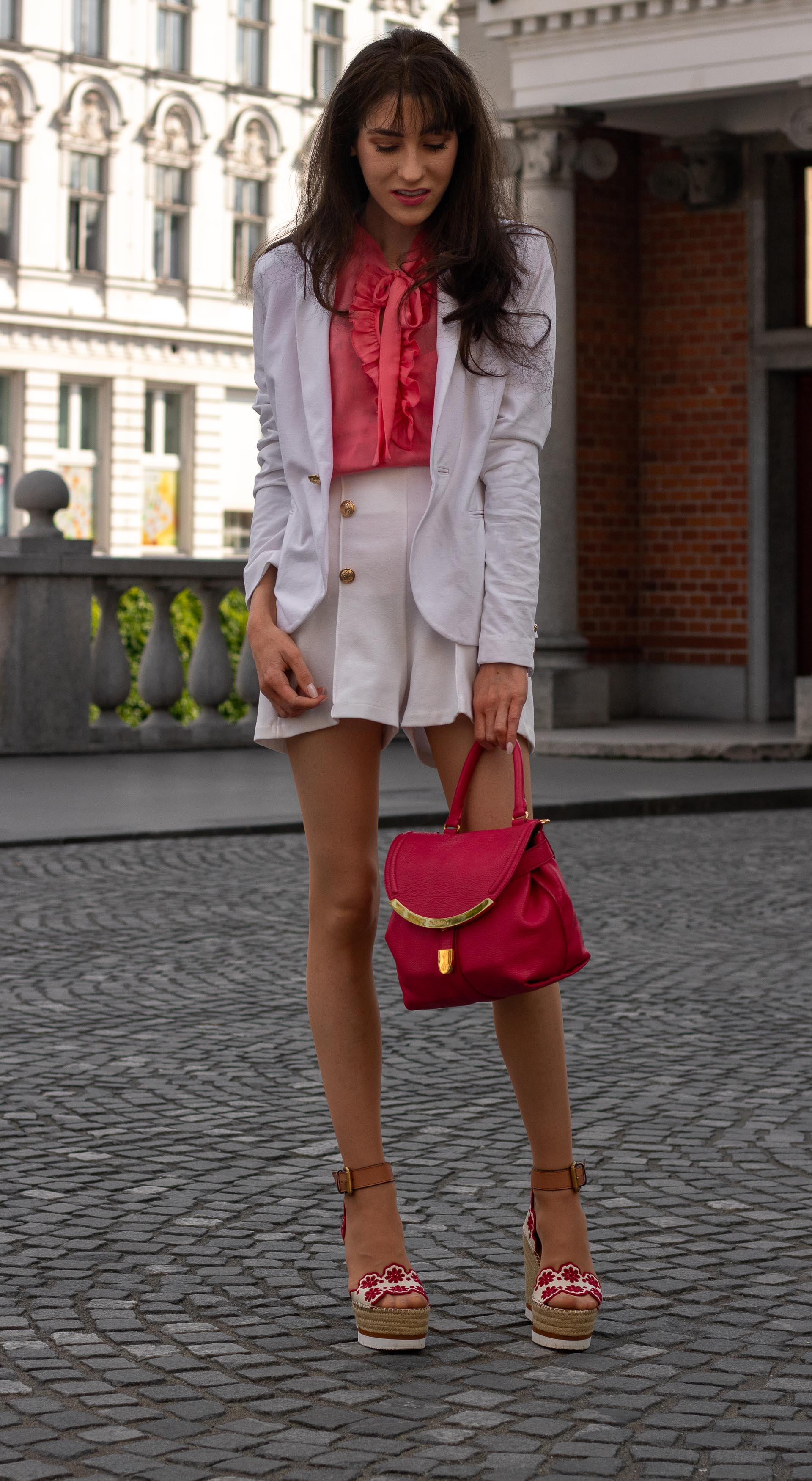 Fashion Blogger Veronika Lipar of Brunette from Wall Street dressed in See by Chloé wedge espadrille white shorts white blazer orange pussy-bow tie blouse pink top handle bag in the city