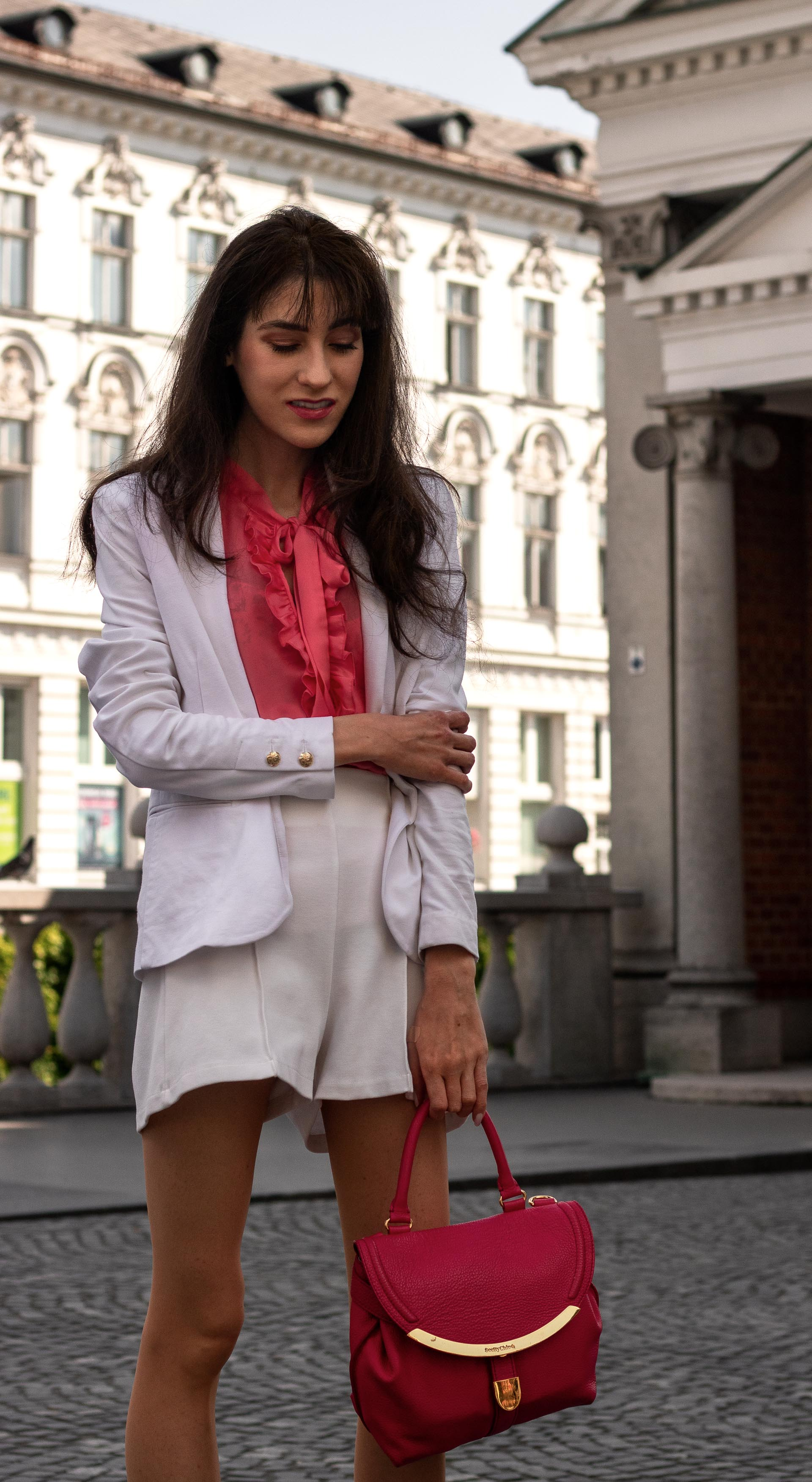 Fashion Blogger Veronika Lipar of Brunette from Wall Street wearing white shorts white blazer orange pussy-bow blouse pink top handle bag in the city