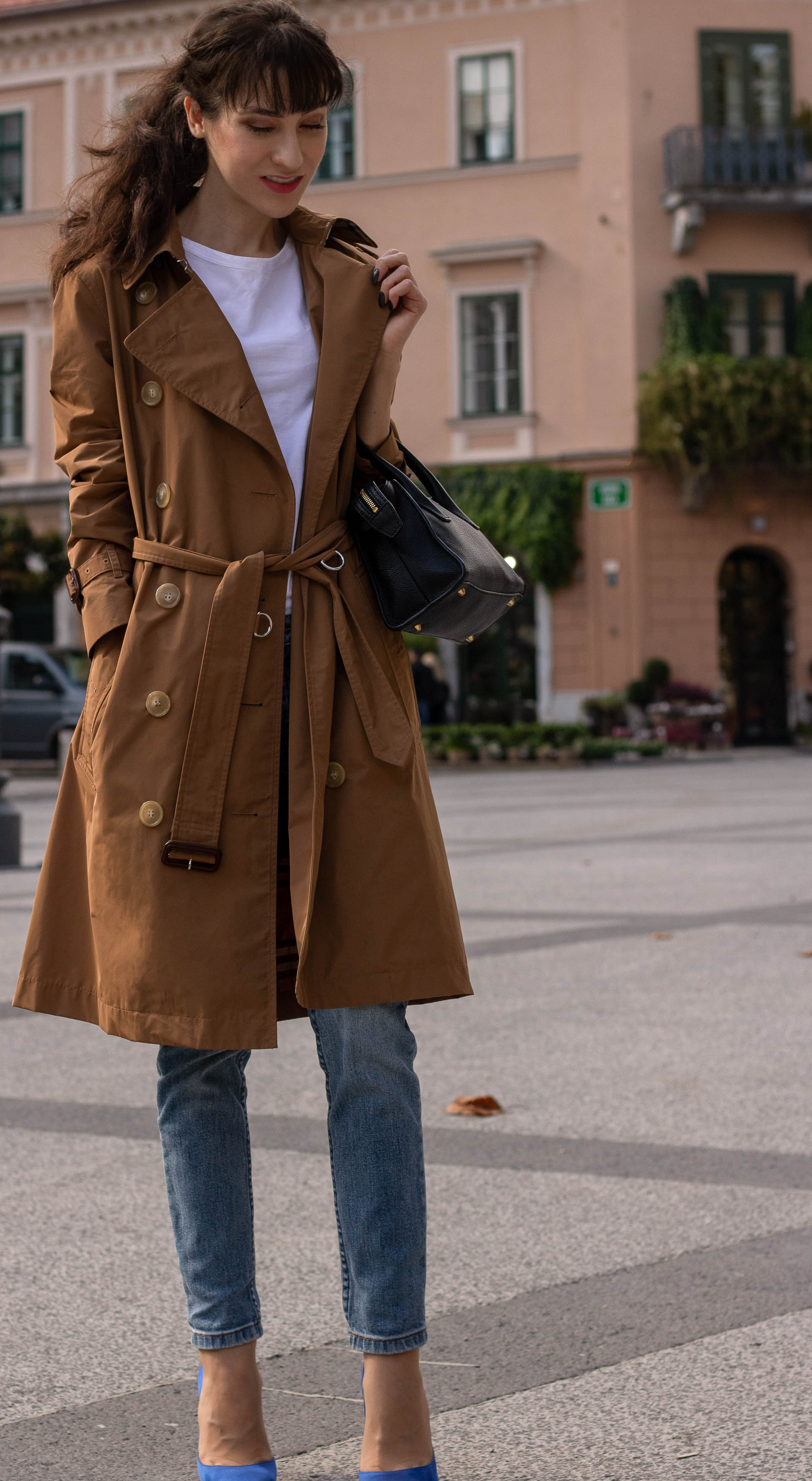 Fashion blogger Veronika Lipar of Brunette from Wall Street wearing white T-shirt blue jeans with camel Burberry trench coat blue Gianvito Rossi pumps black top handle bag in fall