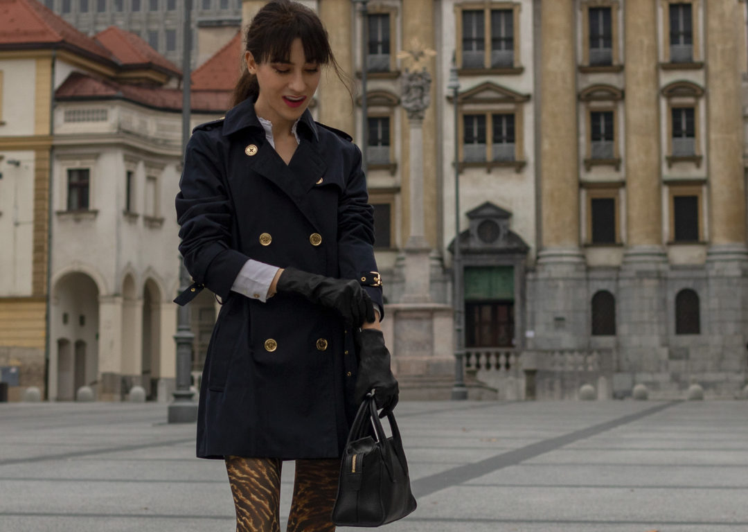 Fashion blogger Veronika Lipar of Brunette from Wall Street dressed in black short trench coat Ganni animal print stockings small black gloves for a night out with friends