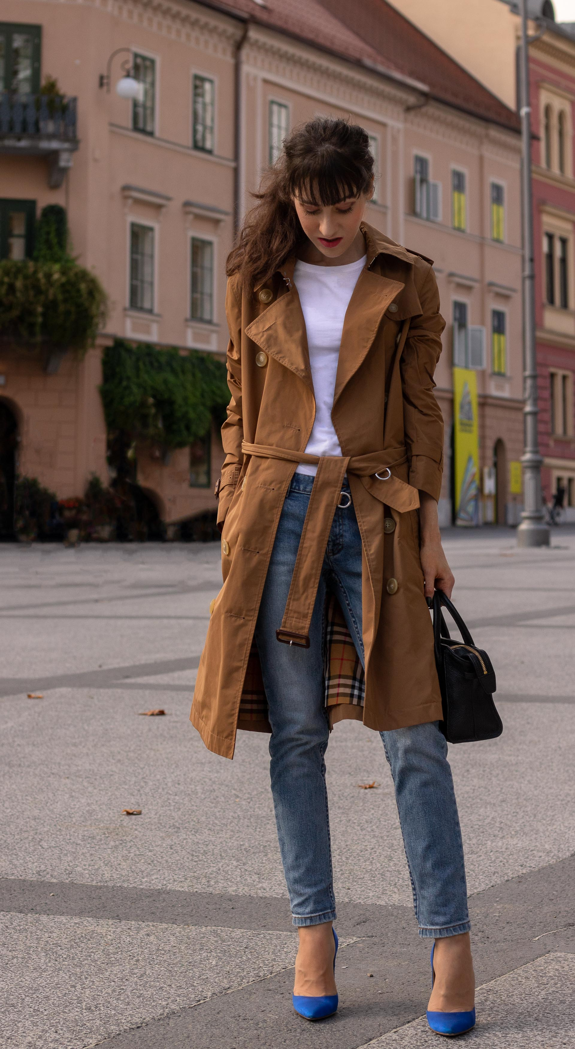 Fashion blogger Veronika Lipar of Brunette from Wall Street dressed in white T-shirt blue jeans with camel Burberry trench coat blue Gianvito Rossi pumps black top handle bag in fall