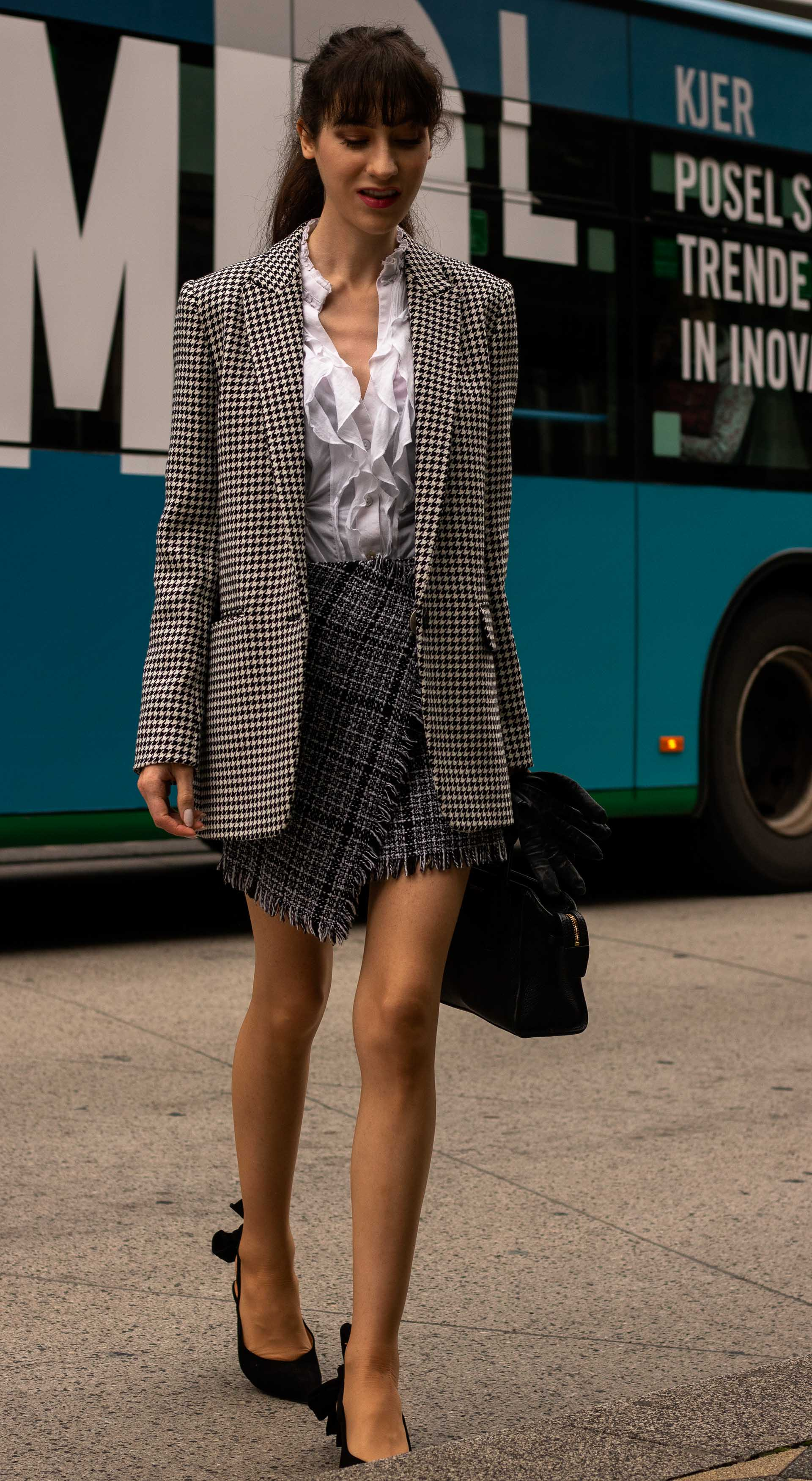 Fashion blogger Veronika Lipar of Brunette from Wall Street wearing Sandro Paris houndstooth blazer white blouse asymmetrical plaid mini skirt Ganni black slingbacks black top handle bag bangs ponytail stepping out off the bus