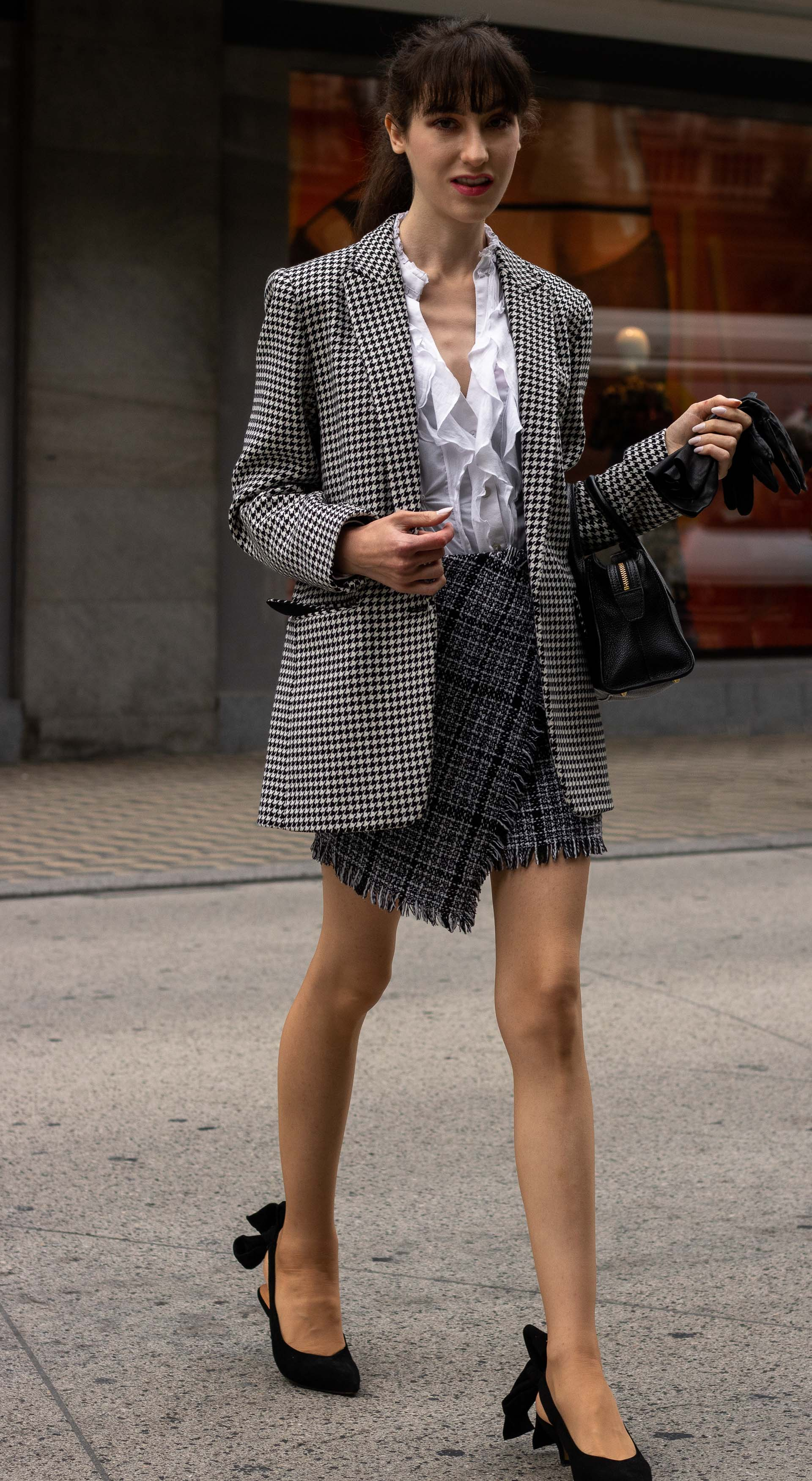Fashion blogger Veronika Lipar of Brunette from Wall Street wearing Sandro Paris houndstooth jacket white blouse plaid mini skirt Ganni black slingbacks black top handle bag bangs ponytail going to work