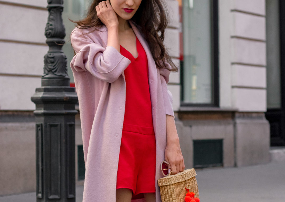 Fashion blogger Veronika Lipar of Brunette from Wall Street dressed in pink cocoon wool coat Harris Wharf London red romper basket bag between seasons