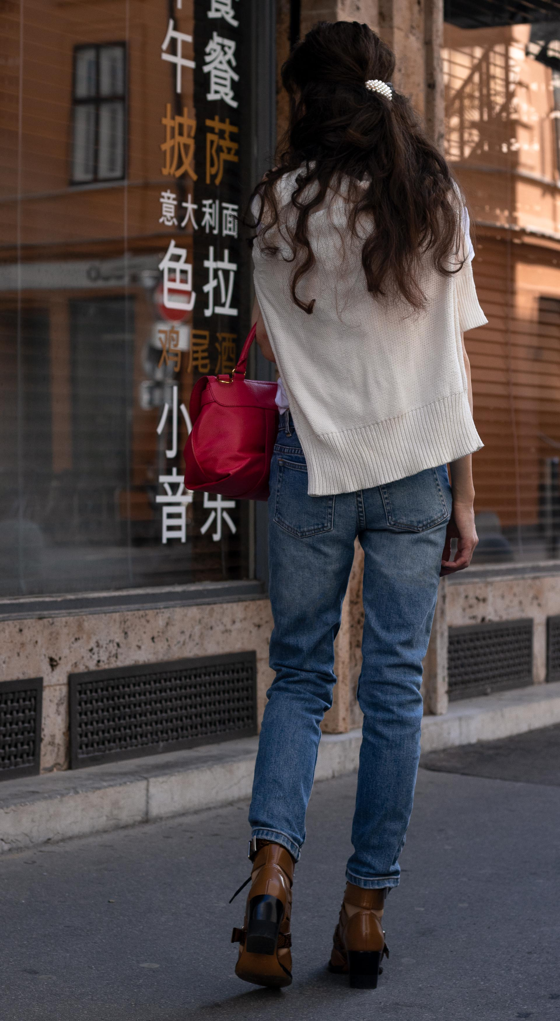 Fashion blogger Veronika Lipar of Brunette from Wall Street dressed in blue jeans white T-shirt under sweater set tied around her neck pink top handle bag Chloé Rylee brown boots in fall