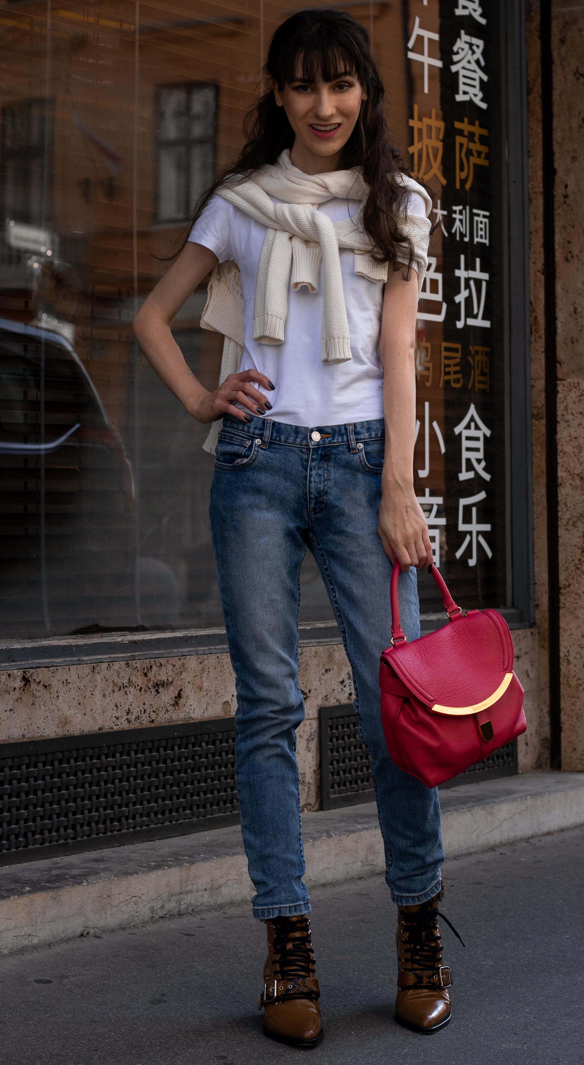 Fashion blogger Veronika Lipar of Brunette from Wall Street wearing blue jeans white T-shirt under sweater set tied around her neck pink top handle bag Chloé Rylee brown boots in fall