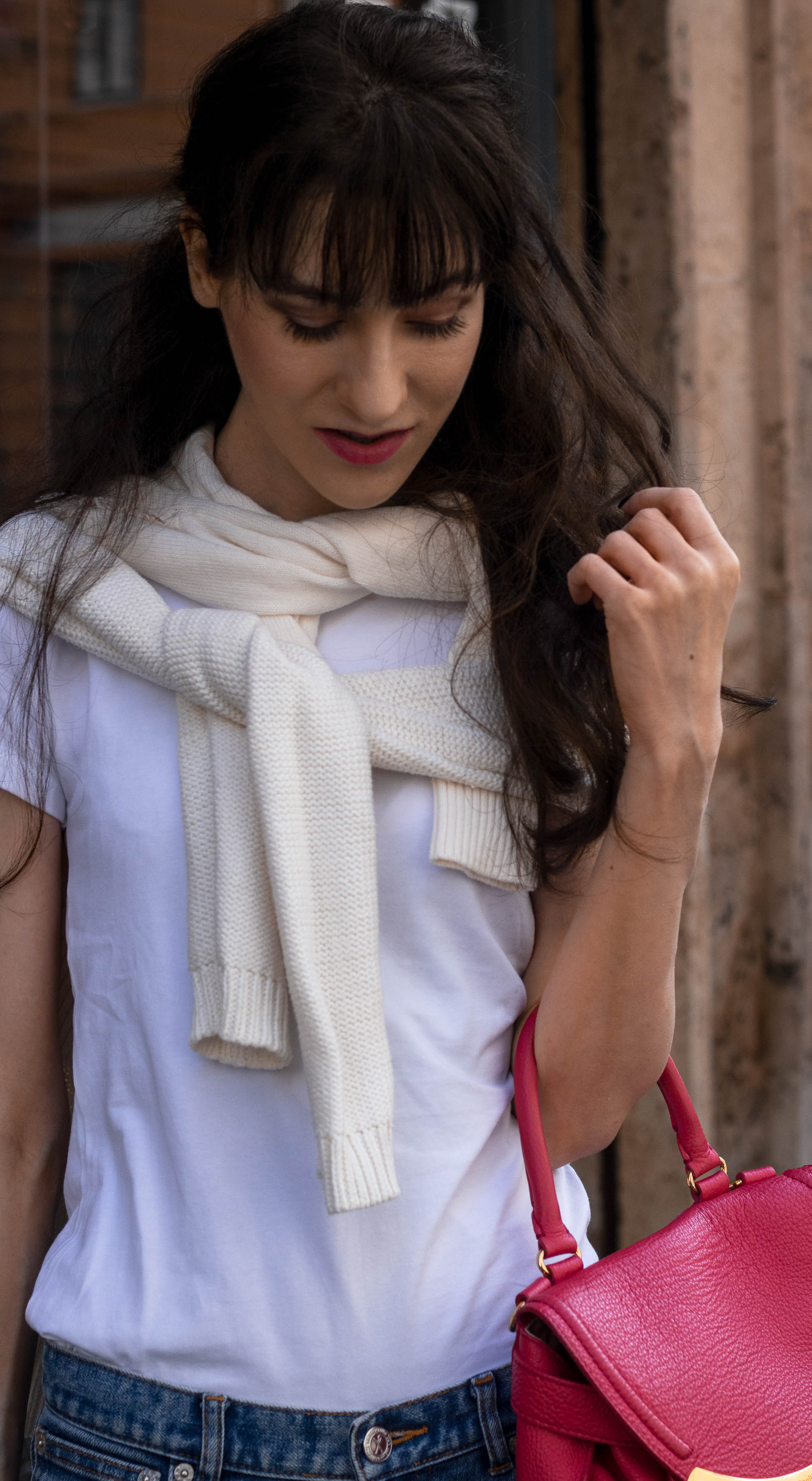 Fashion blogger Veronika Lipar of Brunette from Wall Street wearing blue jeans white T-shirt under sweater tied around her neck pink top handle bag in fall