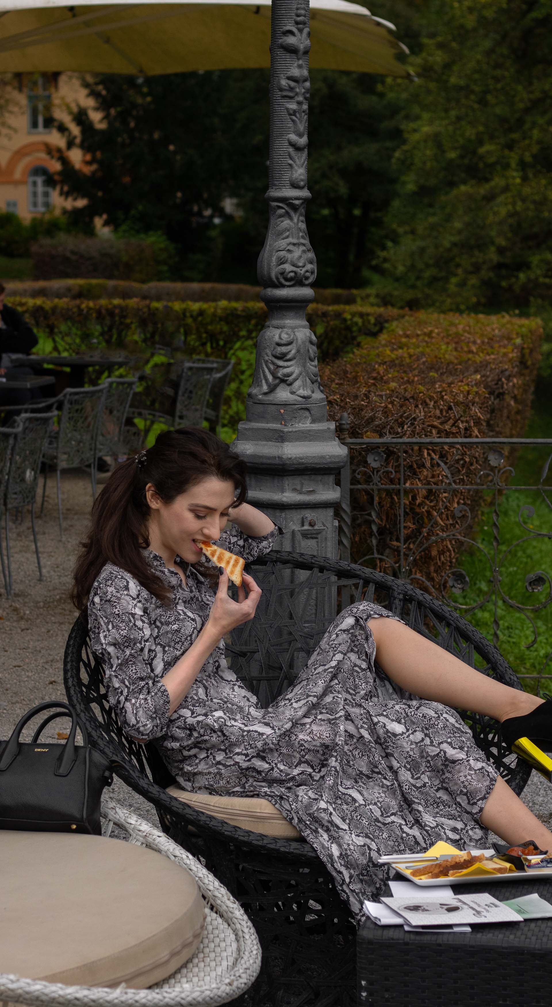 Fashion blogger Veronika Lipar of Brunette from Wall Street wearing grey long snakeskin print dress black Fendi ankle boots with golden heels eating peanut & jelly toast at brunch with girlfriends in fall