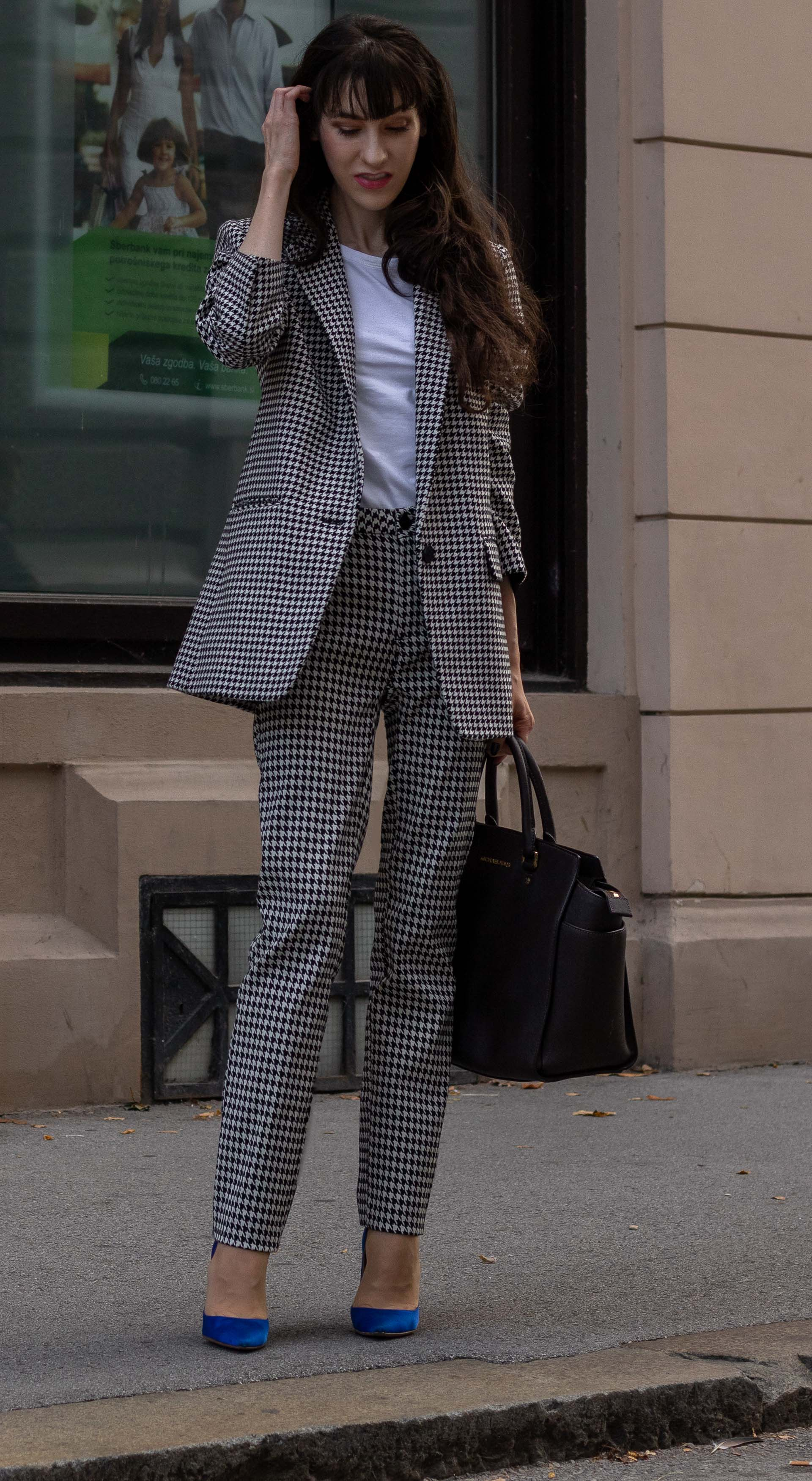 Fashion blogger Veronika Lipar of Brunette from Wall Street dressed in white Sandro houndstooth tailored blazer European Culture houndstooth pants Michael Kors Selma bag blue Gianvito Rossi court shoes for work in fall