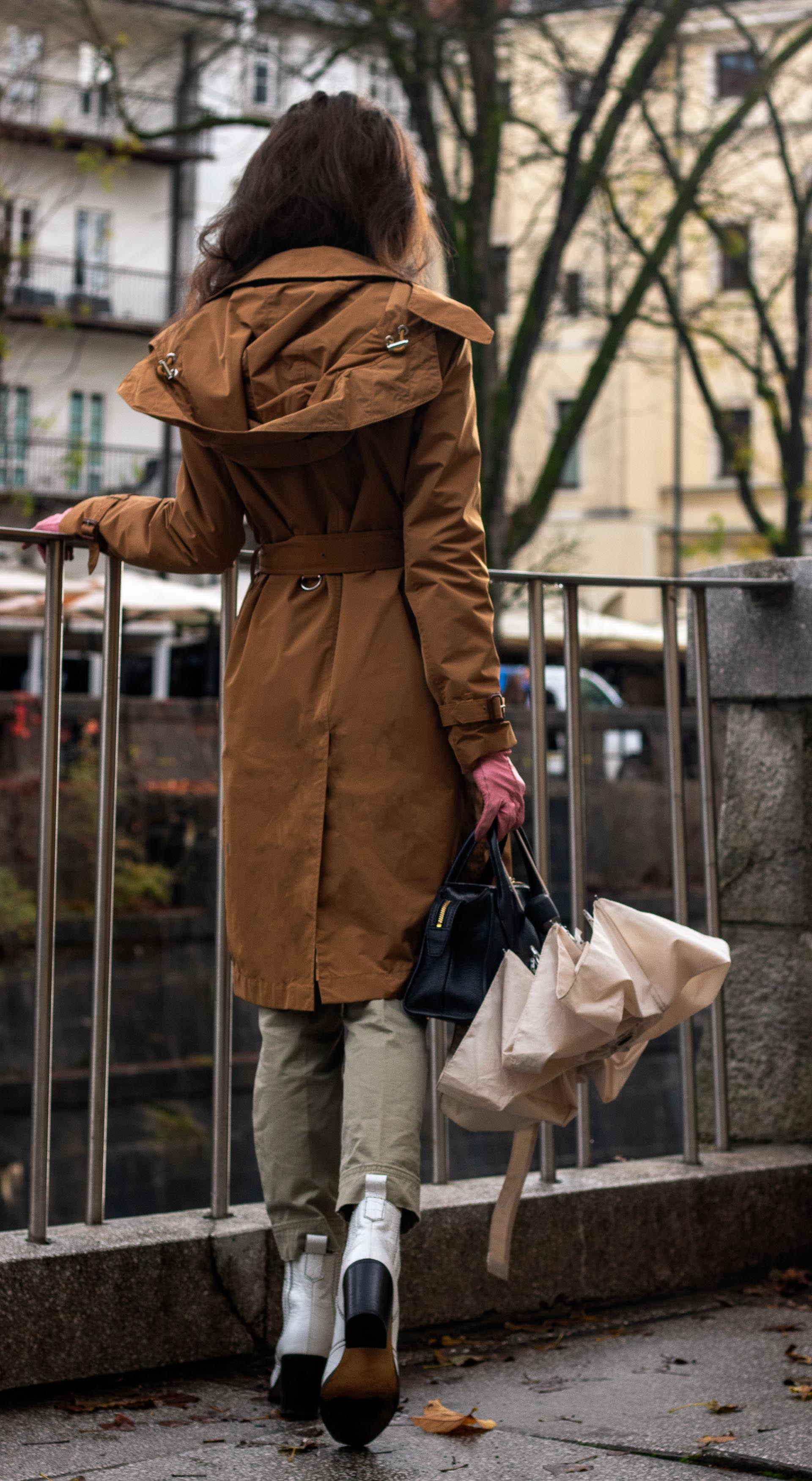 Fashion blogger Veronika Lipar of Brunette from Wall Street wearing white Ganni cowboy boots camel Burberry trench coat Re/Done cargo pants pink gloves umbrella in the rain