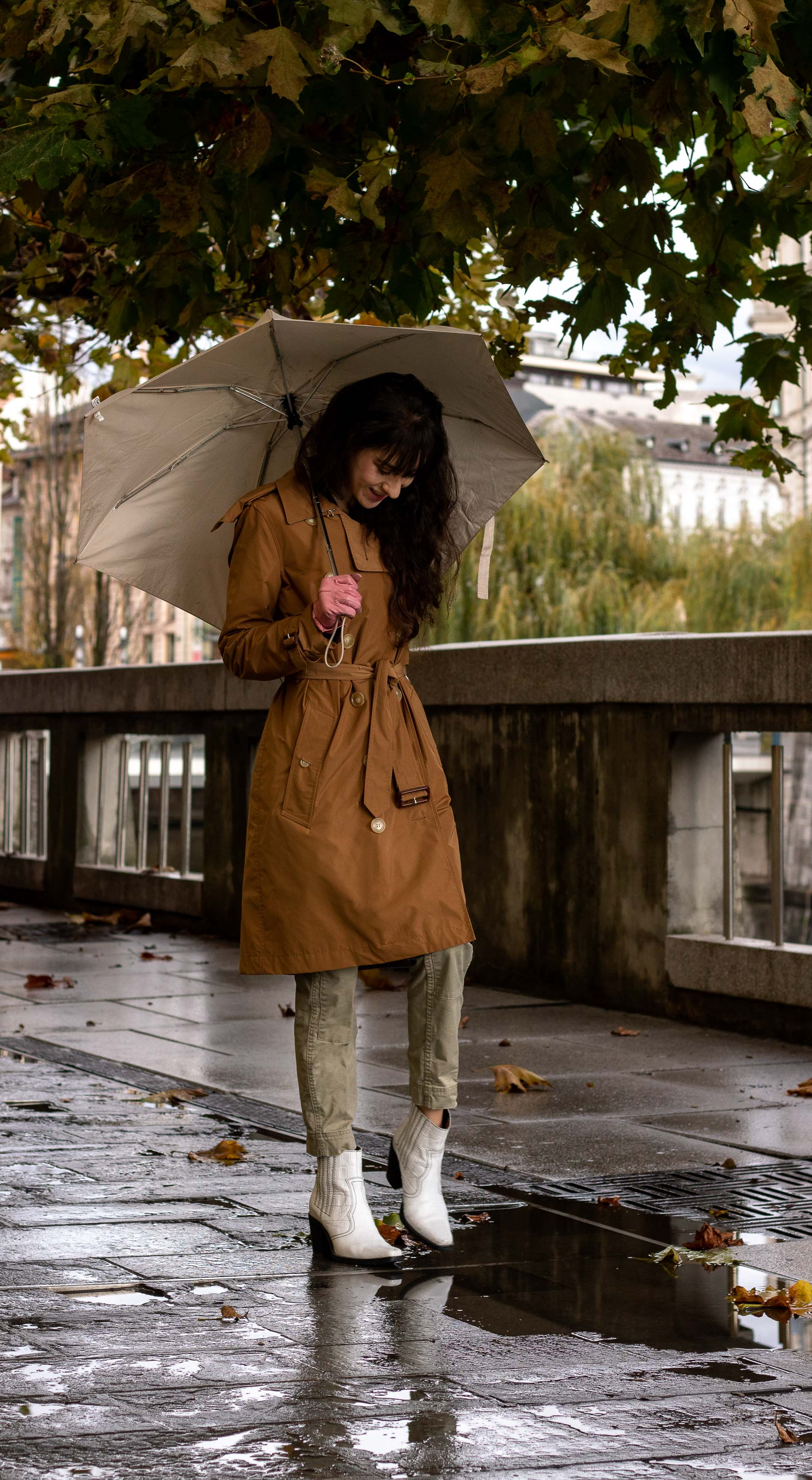 Fashion blogger Veronika Lipar of Brunette from Wall Street wearing white Ganni ankle boots camel Burberry trench coat Re/Done cargo pants pink gloves umbrella in the rain