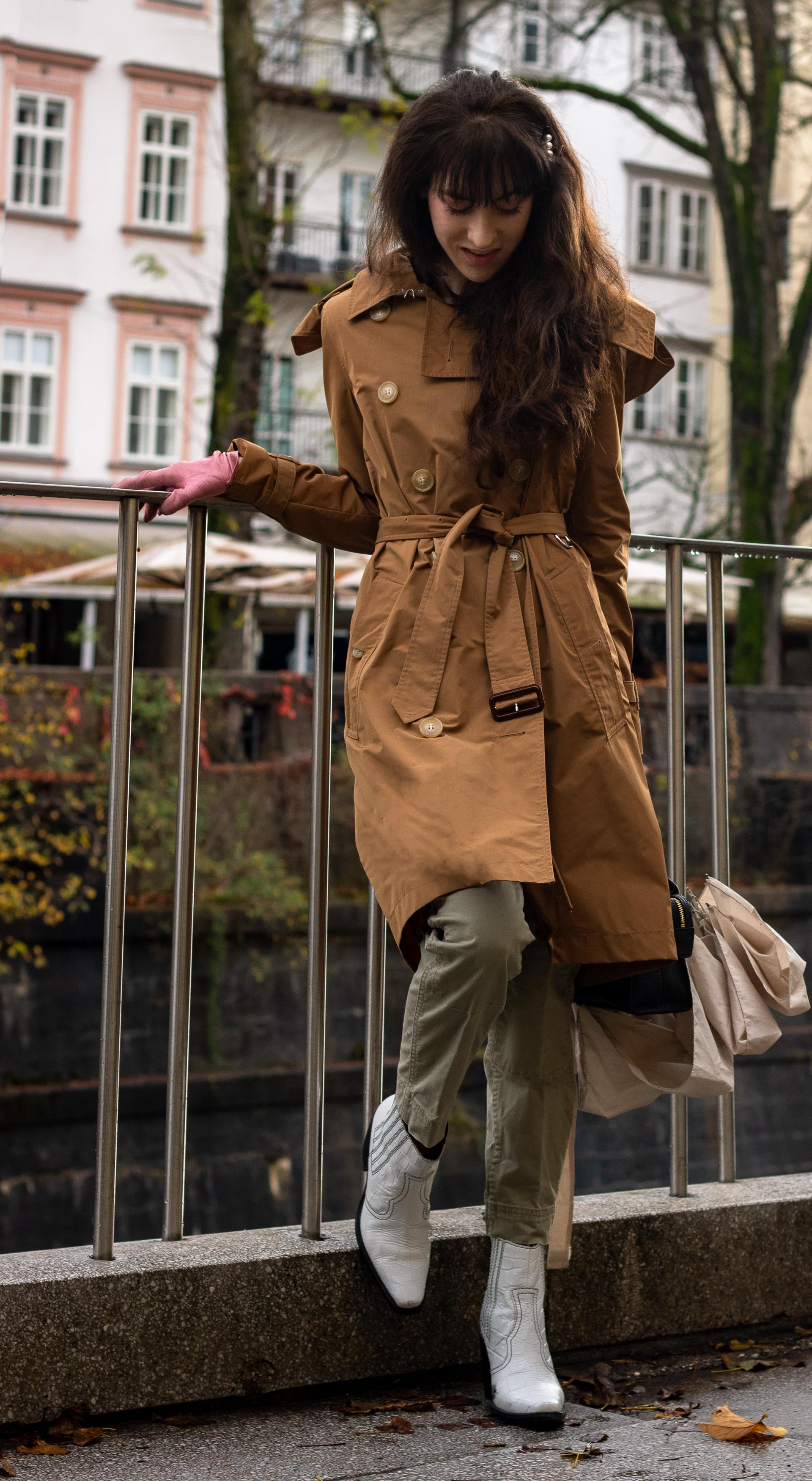 Fashion blogger Veronika Lipar of Brunette from Wall Street wearing white Ganni booties camel Burberry trench coat Re/Done cargo pants pink gloves umbrella in the rain