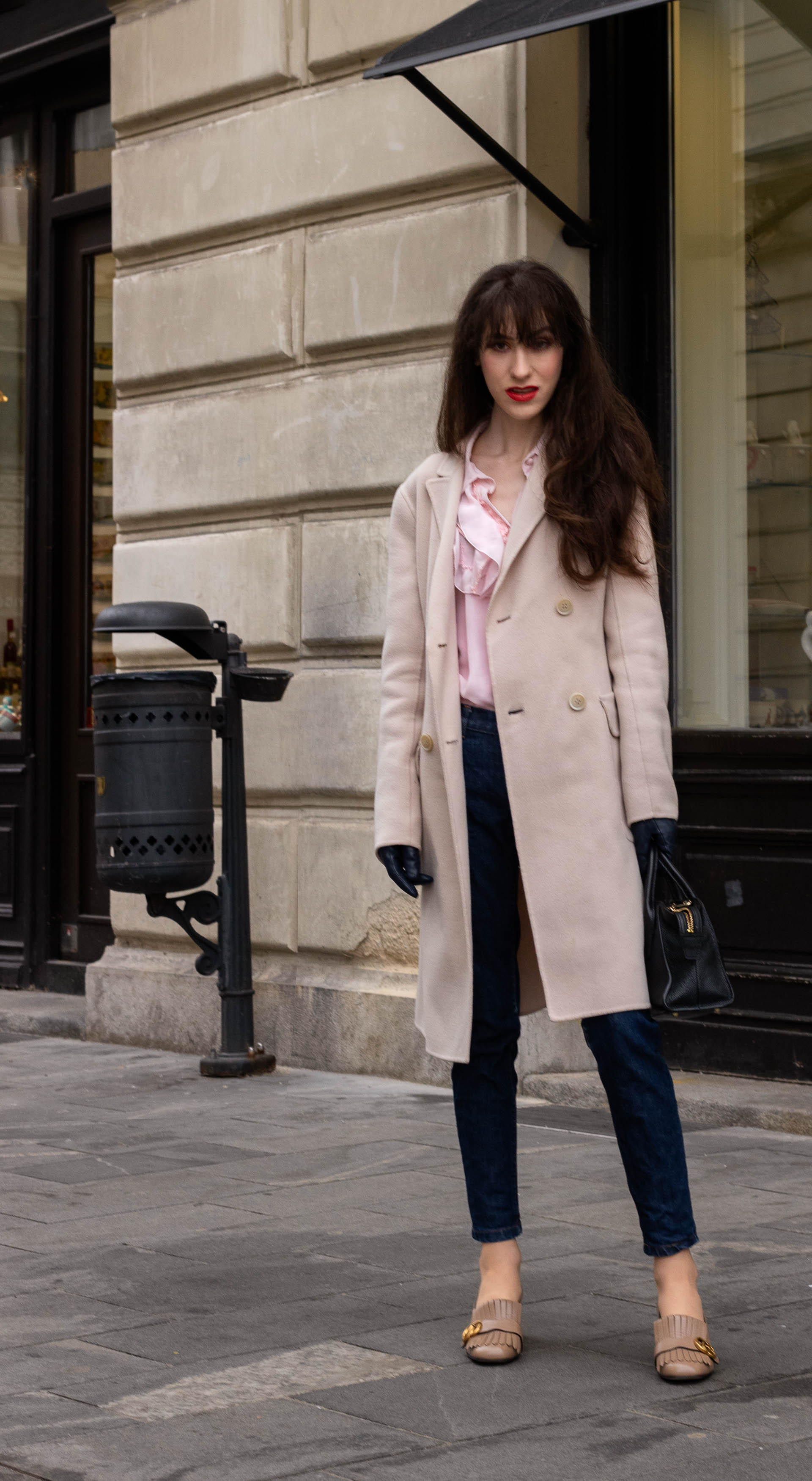 Fashion blogger Veronika Lipar of Brunette from Wall Street wearing pink Gucci heeled loafer A.P.C. navy blue jeans Weekend Max Mara double breasted coat Red Valentino pink blouse black top handle bag blue leather gloves on the street in-between seasons