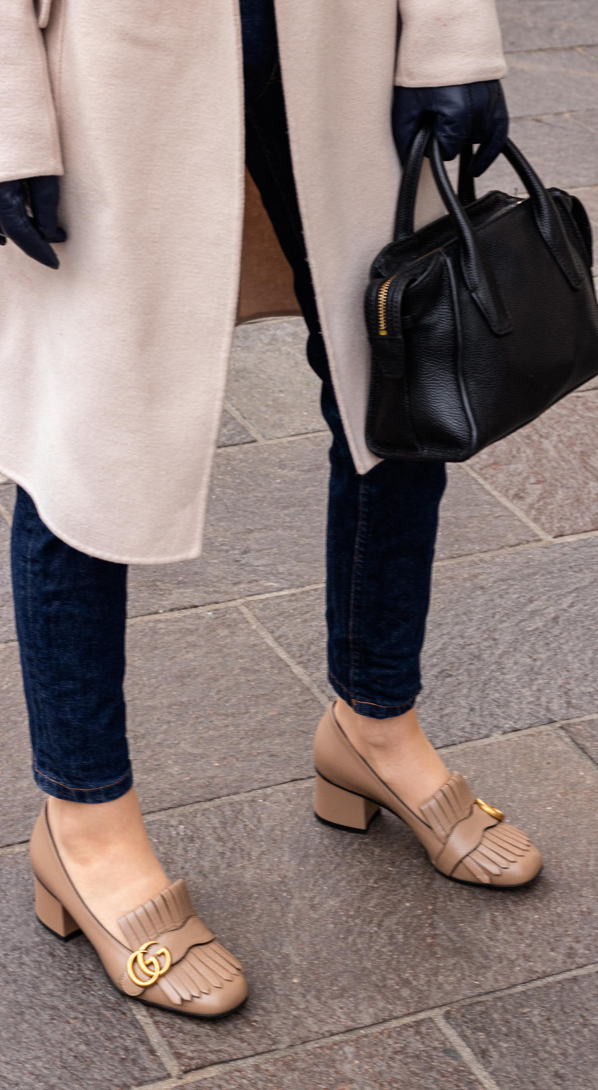 Fashion blogger Veronika Lipar of Brunette from Wall Street wearing simple transitional outfit Gucci heeled loafer A.P.C. navy blue jeans Weekend Max Mara double breasted coat black top handle bag blue leather gloves on the street in-between seasons