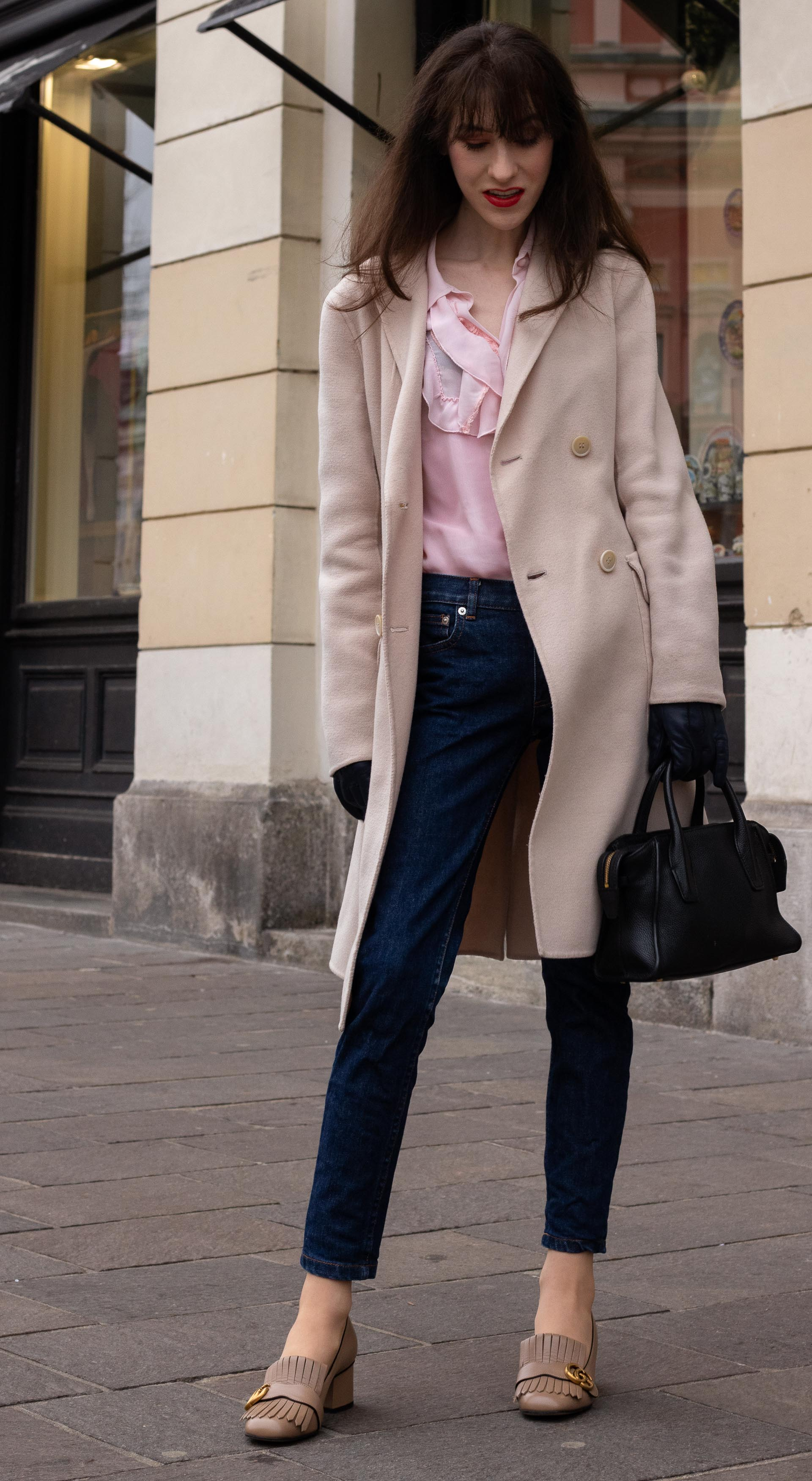 Fashion blogger Veronika Lipar of Brunette from Wall Street dressed in Gucci heeled loafer A.P.C. navy blue jeans Weekend Max Mara double breasted coat Red Valentino pink blouse black top handle bag blue leather gloves on the street in-between seasons