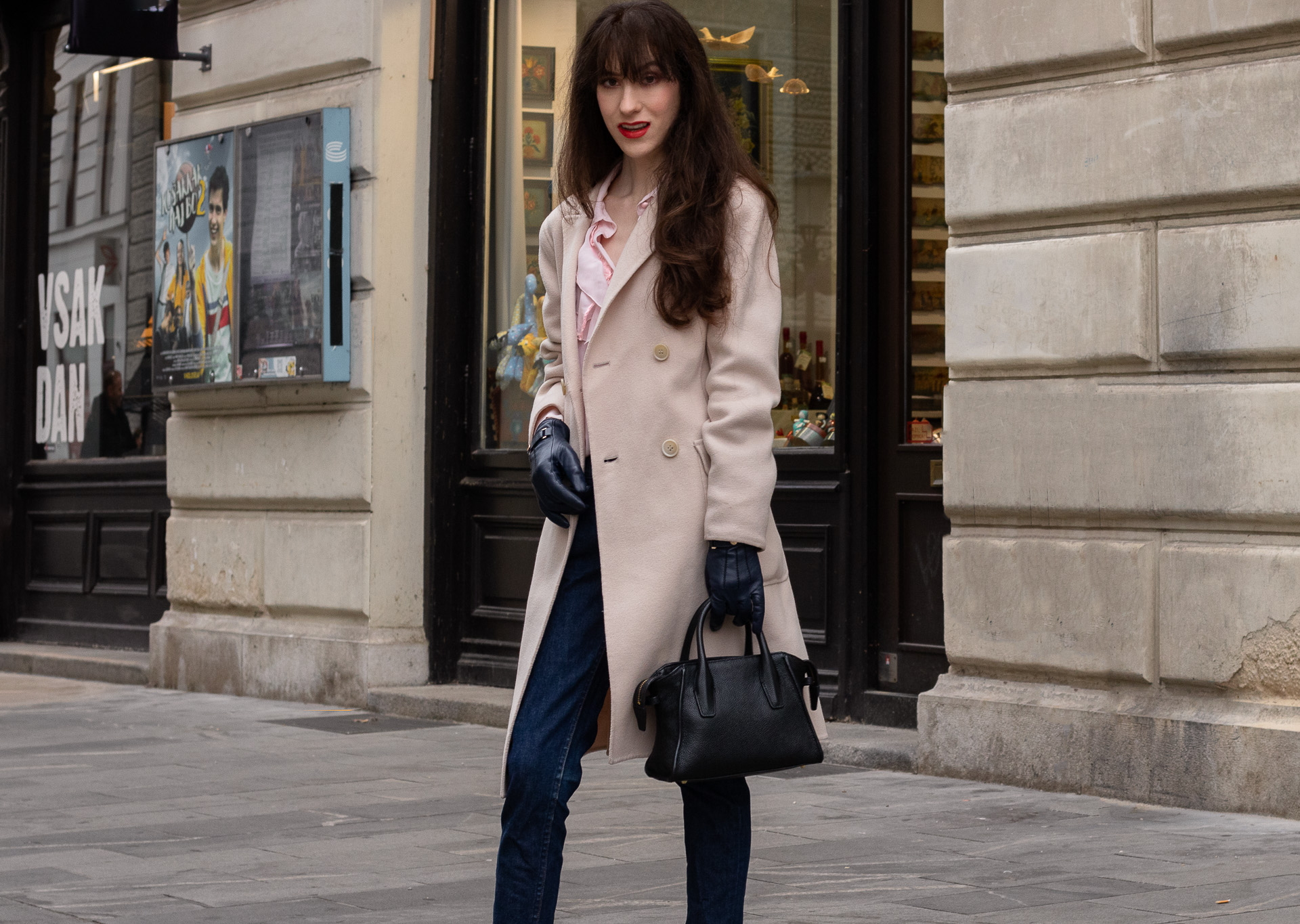 Fashion blogger Veronika Lipar of Brunette from Wall Street dressed in A.P.C. navy blue jeans Weekend Max Mara double breasted coat Red Valentino pink blouse black top handle bag blue leather gloves on the street in-between seasons