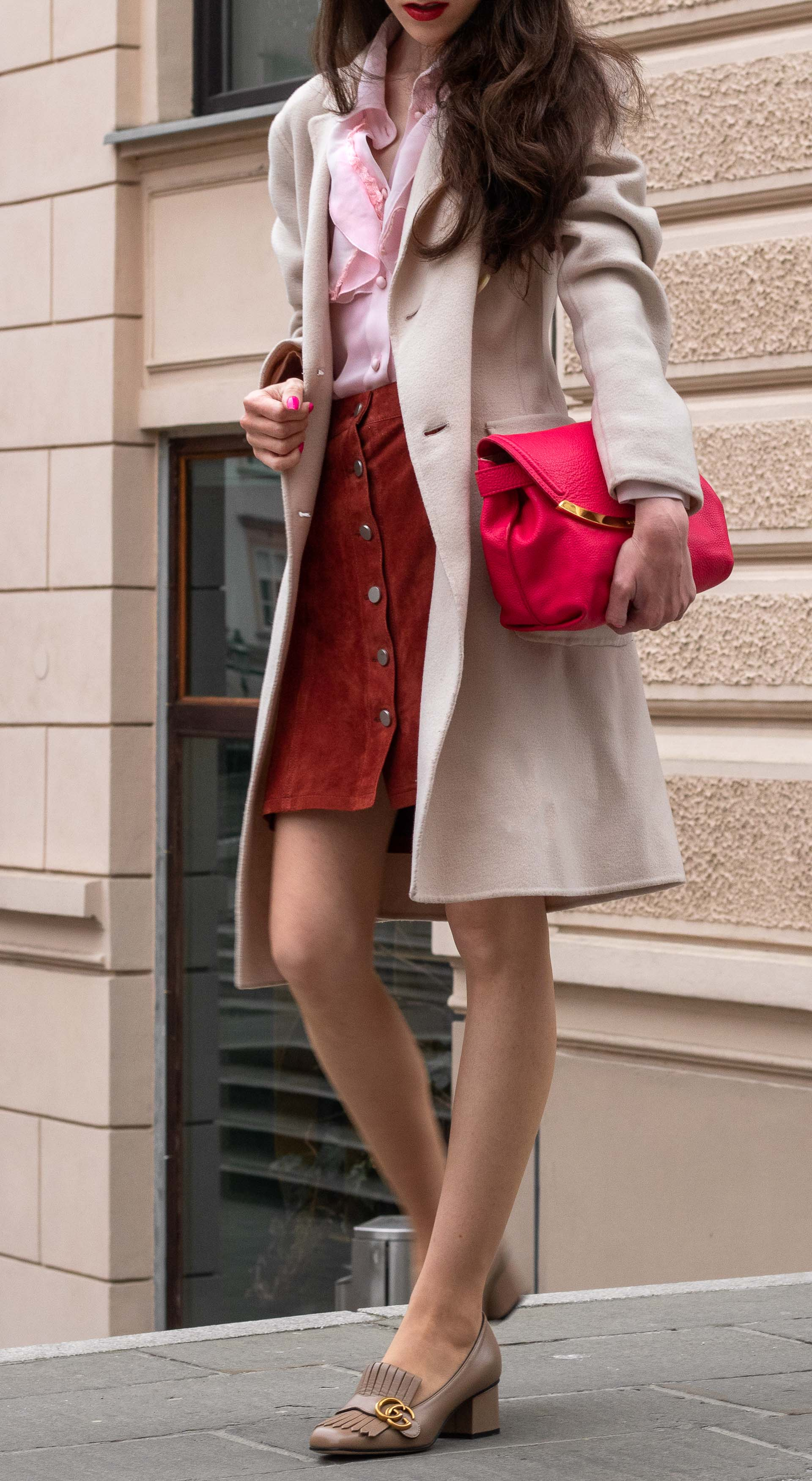 Fashion blogger Veronika Lipar of Brunette from Wall Street dressed in easy transitional outfit Weekend Max Mara double breasted coat Red Valentino pink blouse brown suede front button short skirt pink pouch bag Gucci heeled loafers on the street